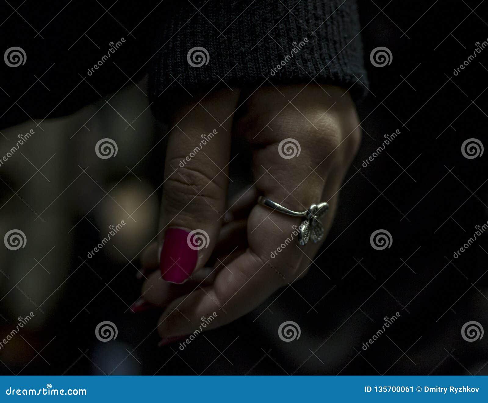 有红色钉子的手在黑暗