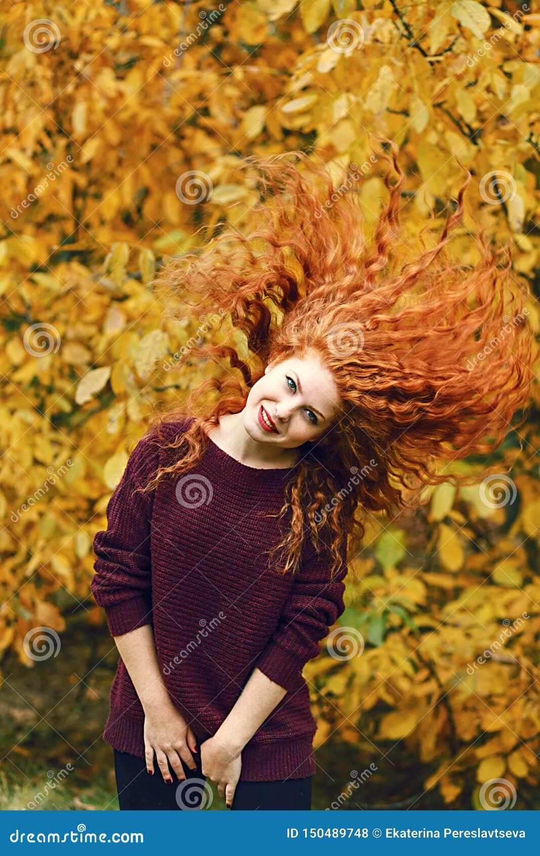 有红色长发的正面美丽的年轻女人在秋天森林背景,头发用不同的方向