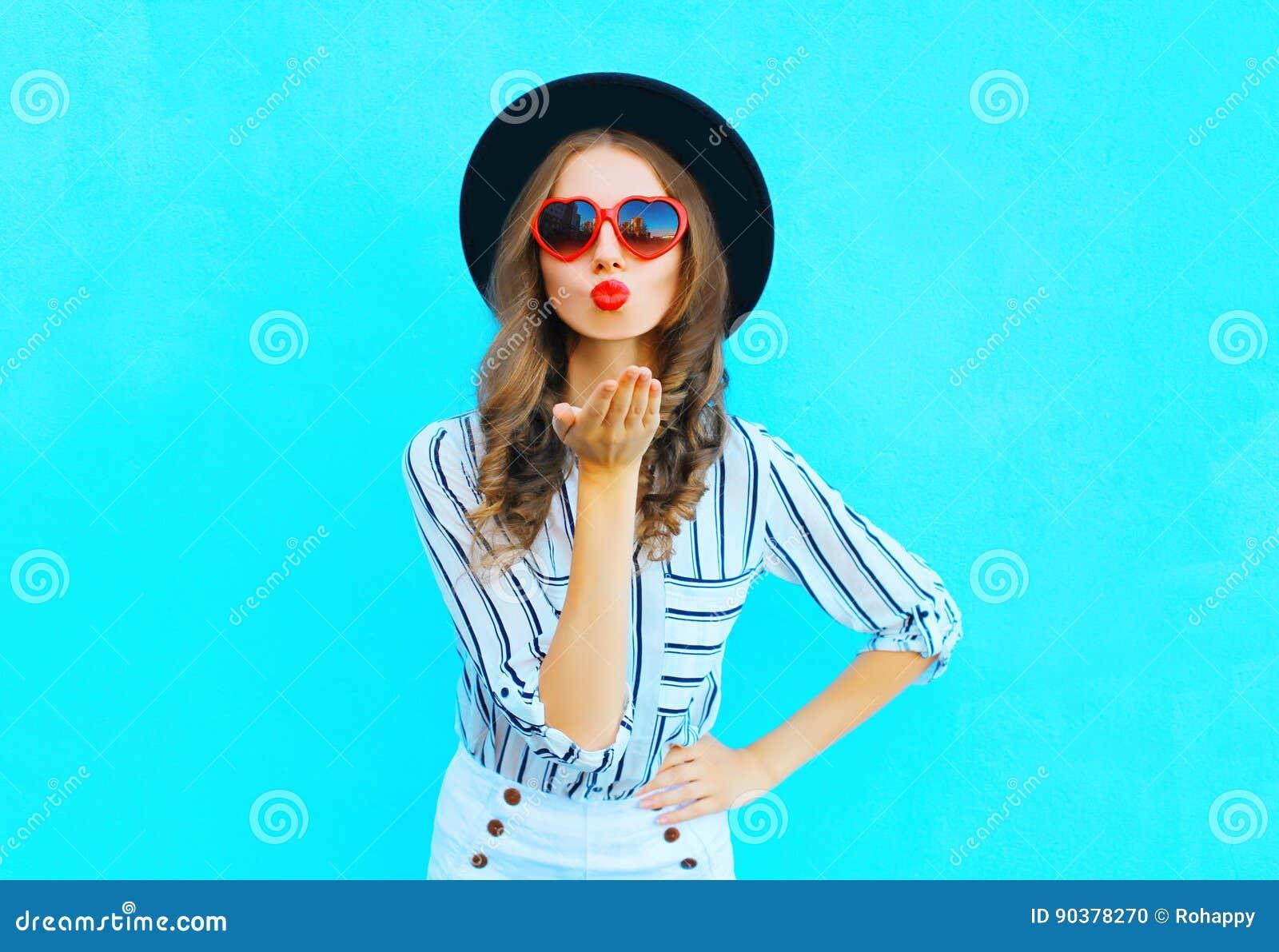 有红色嘴唇的俏丽的妇女是的时尚画象送在心脏太阳镜形状的空气亲吻在蓝色的