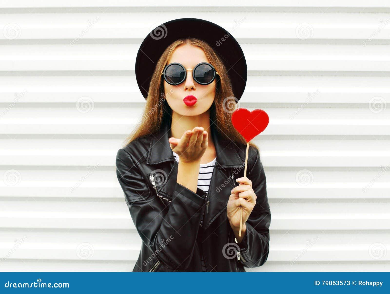 有红色嘴唇的时尚相当甜少妇送与穿在白色的棒棒糖心脏的空气亲吻黑帽会议皮夹克