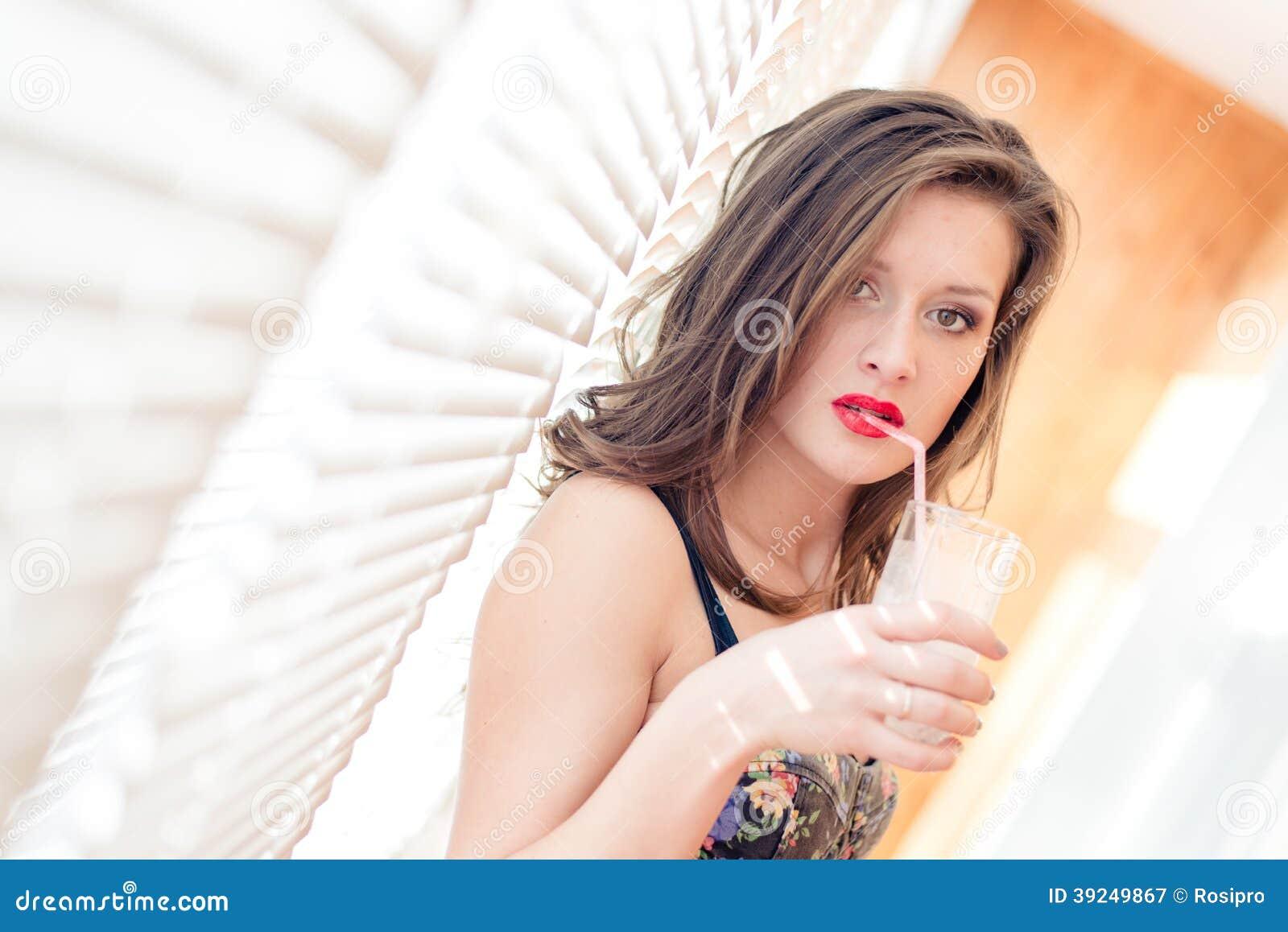 有红色嘴唇的诱人的美丽的年轻深色的妇女喝与从玻璃的秸杆的站立近的窗帘