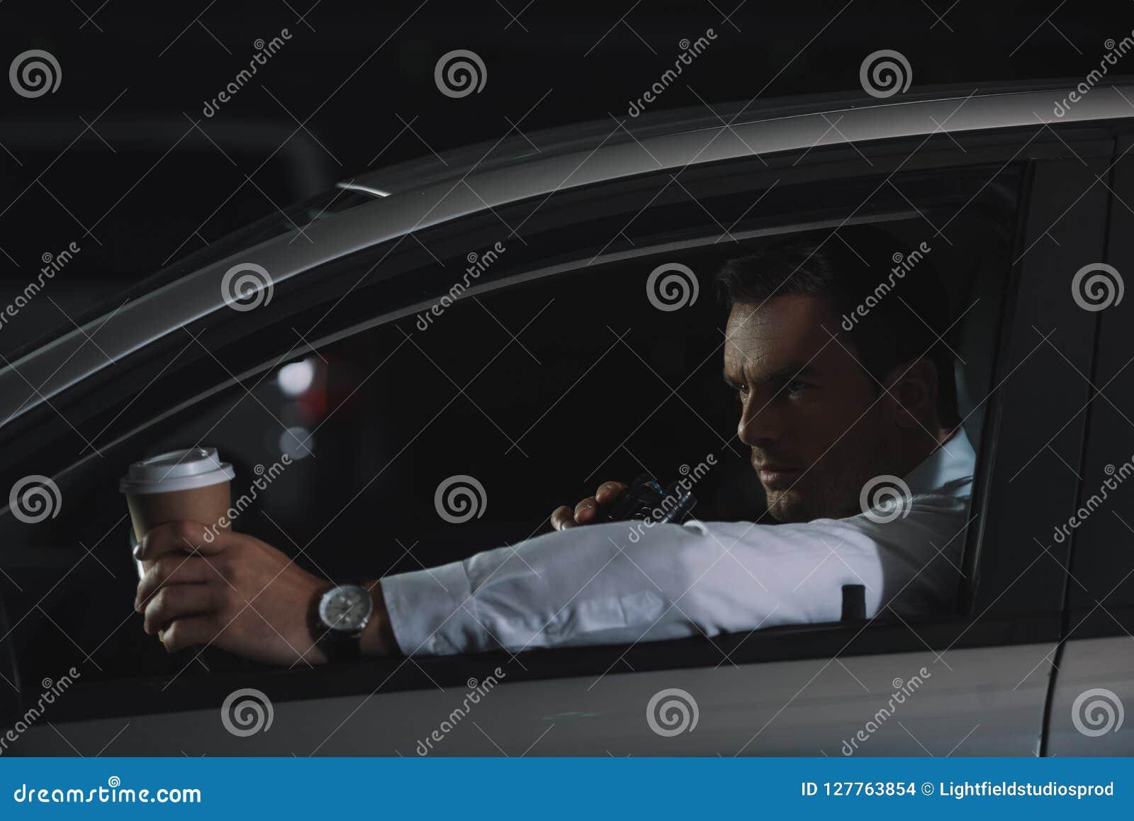 有纸咖啡的男性密探使用有声电影walkie的