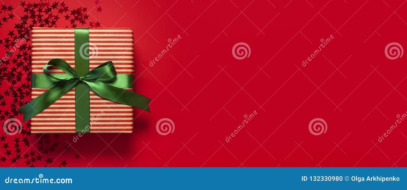 有绿色丝带和星的全息照相的闪烁五彩纸屑形式的礼物盒在红色背景顶视图平的位置的 假日概念,