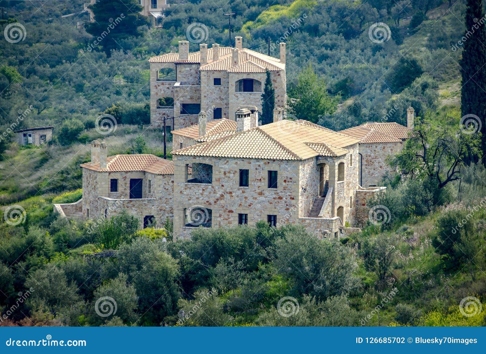 有绿色自然围拢的陶瓷屋顶的新的建造的豪华石房子 希腊
