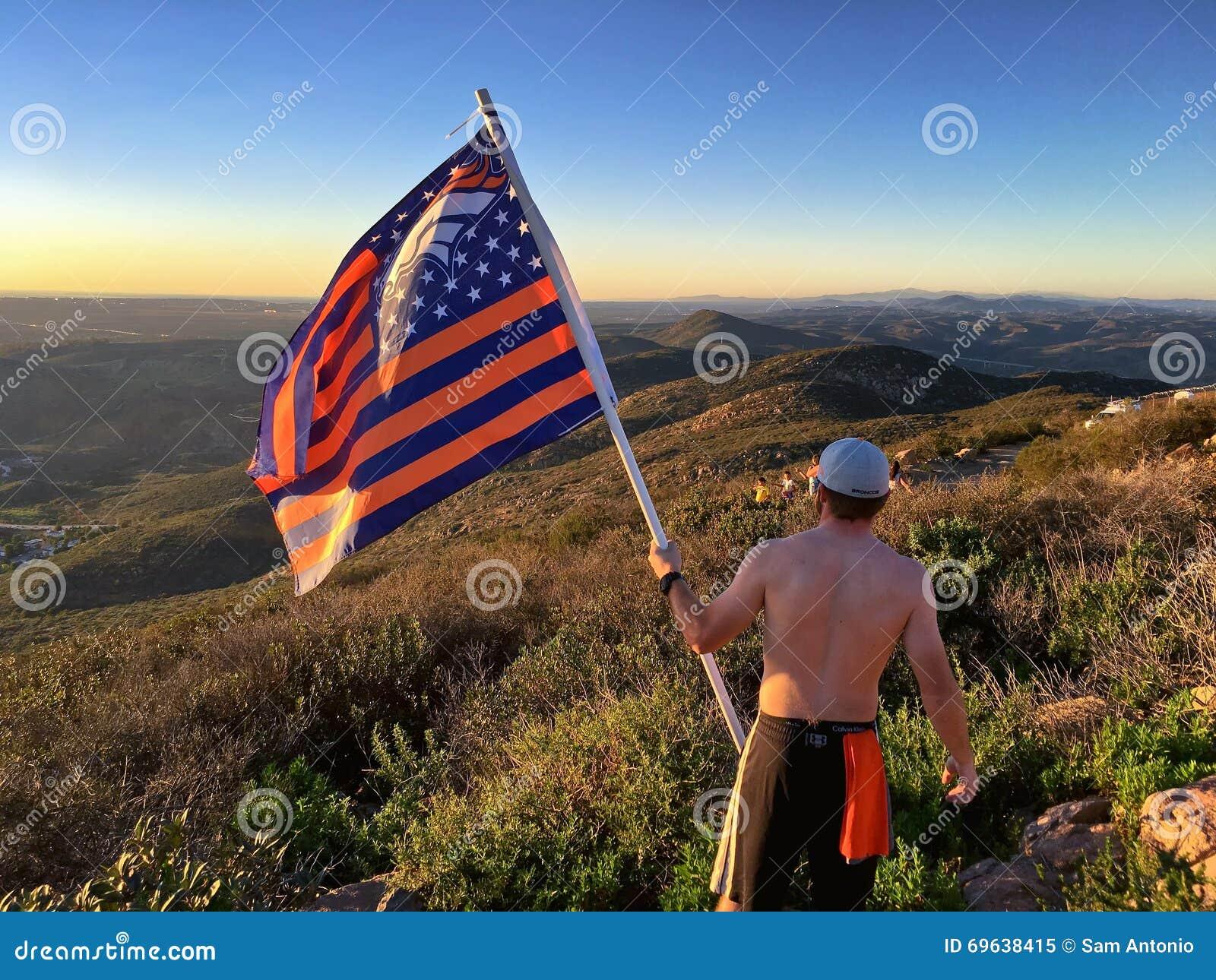 有美国橄榄球联盟丹佛野马旗子的远足者在山山顶