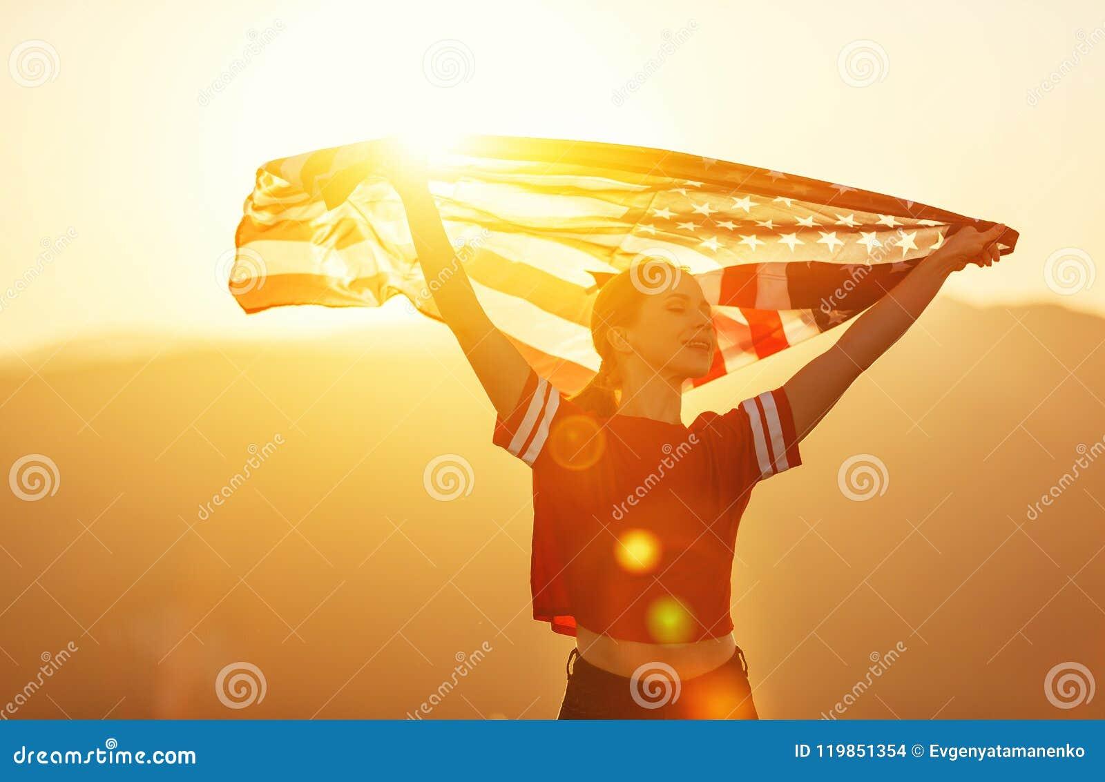 有美国的旗子的愉快的妇女享受在na的日落