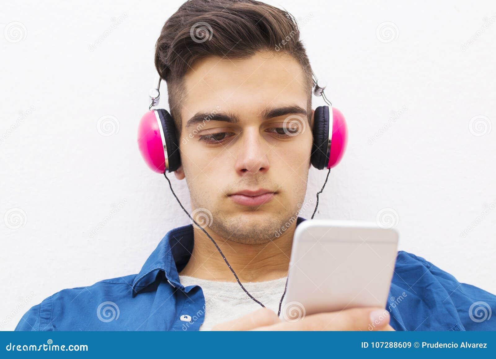 有耳机和手机的严肃的青少年的男孩
