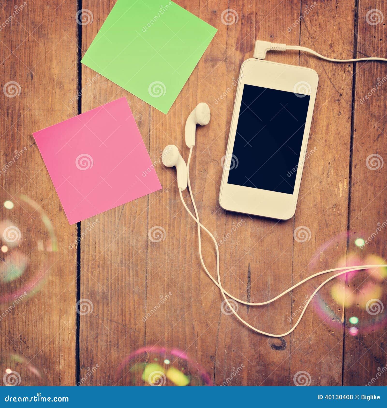 有耳机和稠粘的笔记的智能手机关于木表面