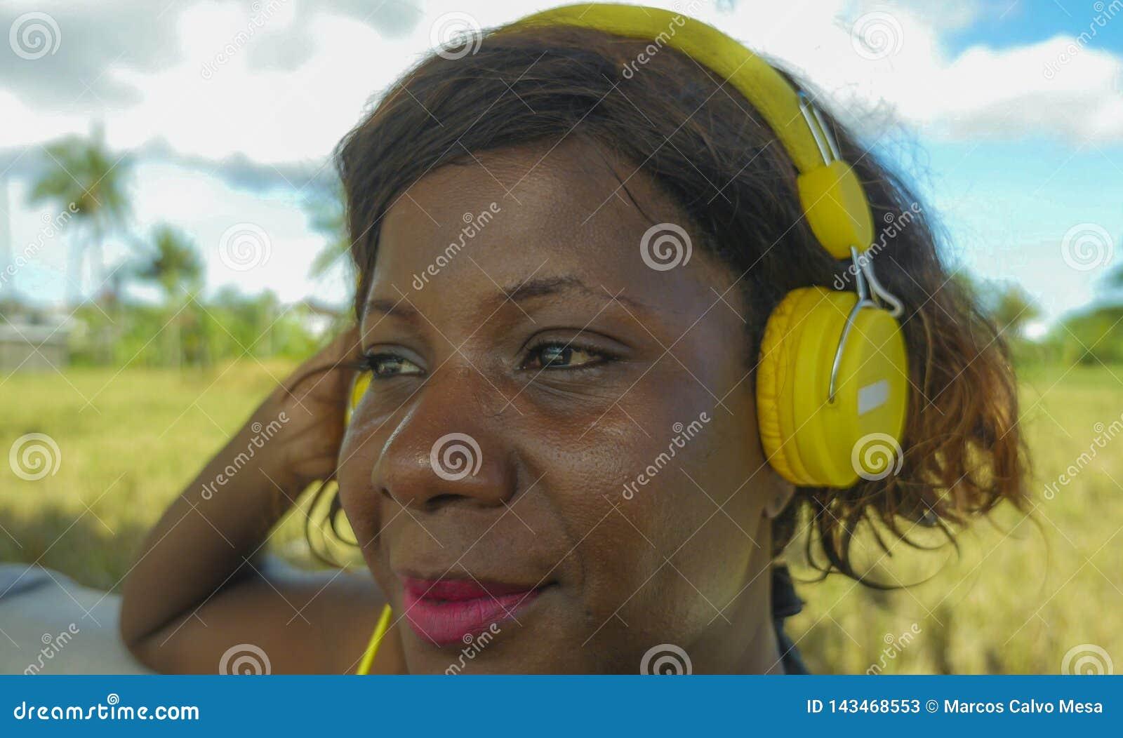 有耳机的年轻美丽和愉快的黑人美国黑人的妇女听到户外音乐的变冷了并且放松了享受夏天