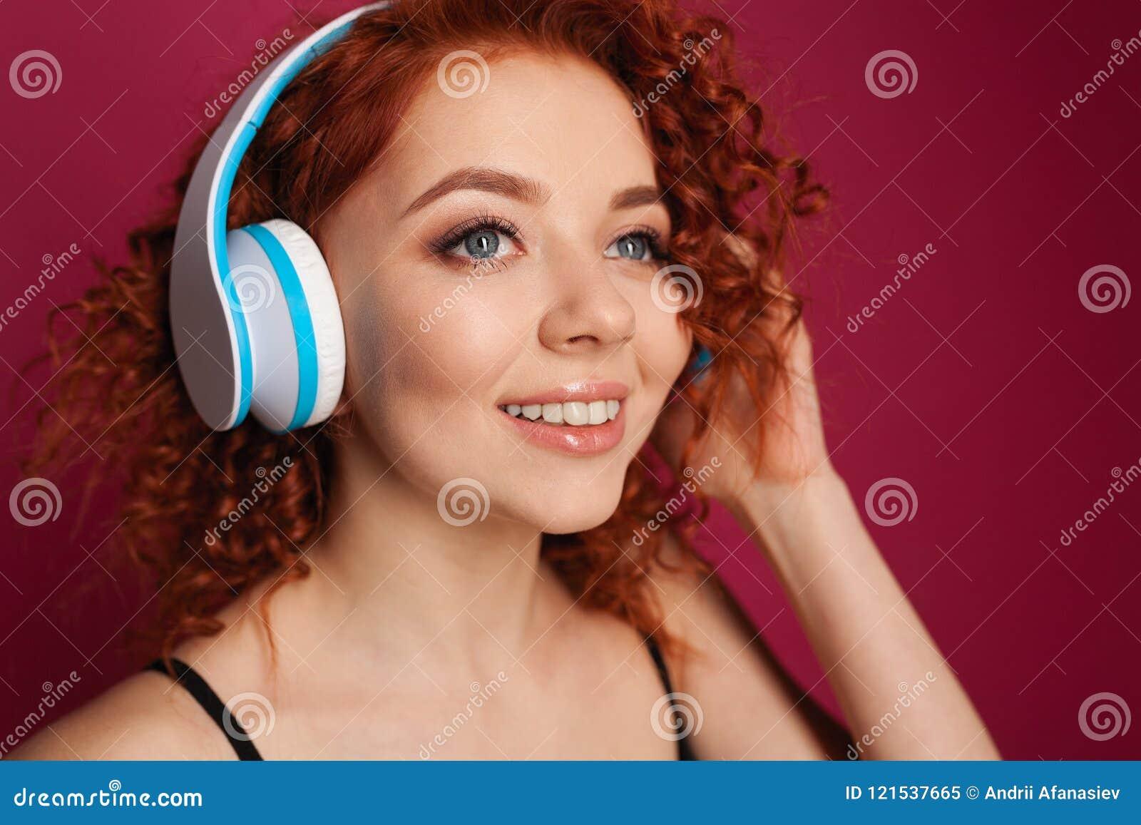 有耳机的美丽的卷发的年轻红发女孩 特写镜头纵向