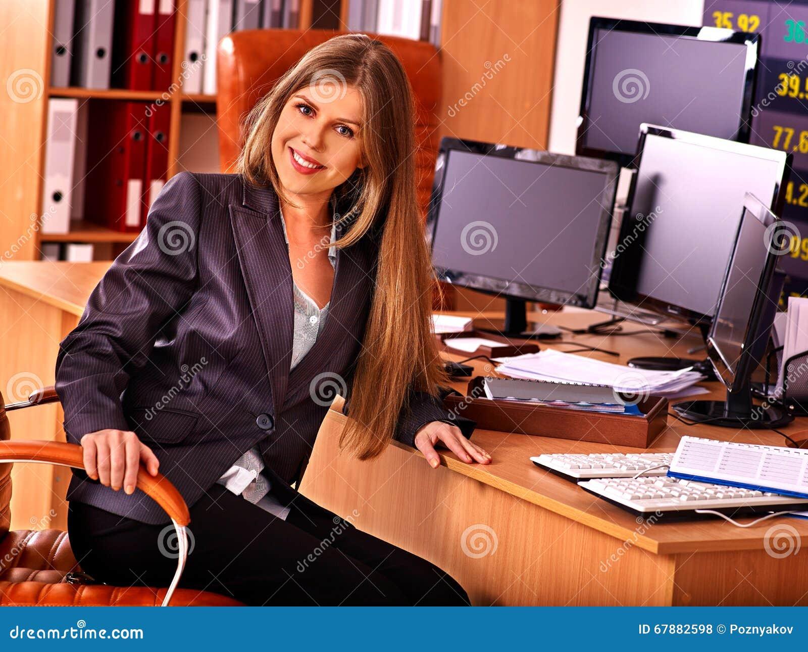 有股票的女商人几台显示器在办公室