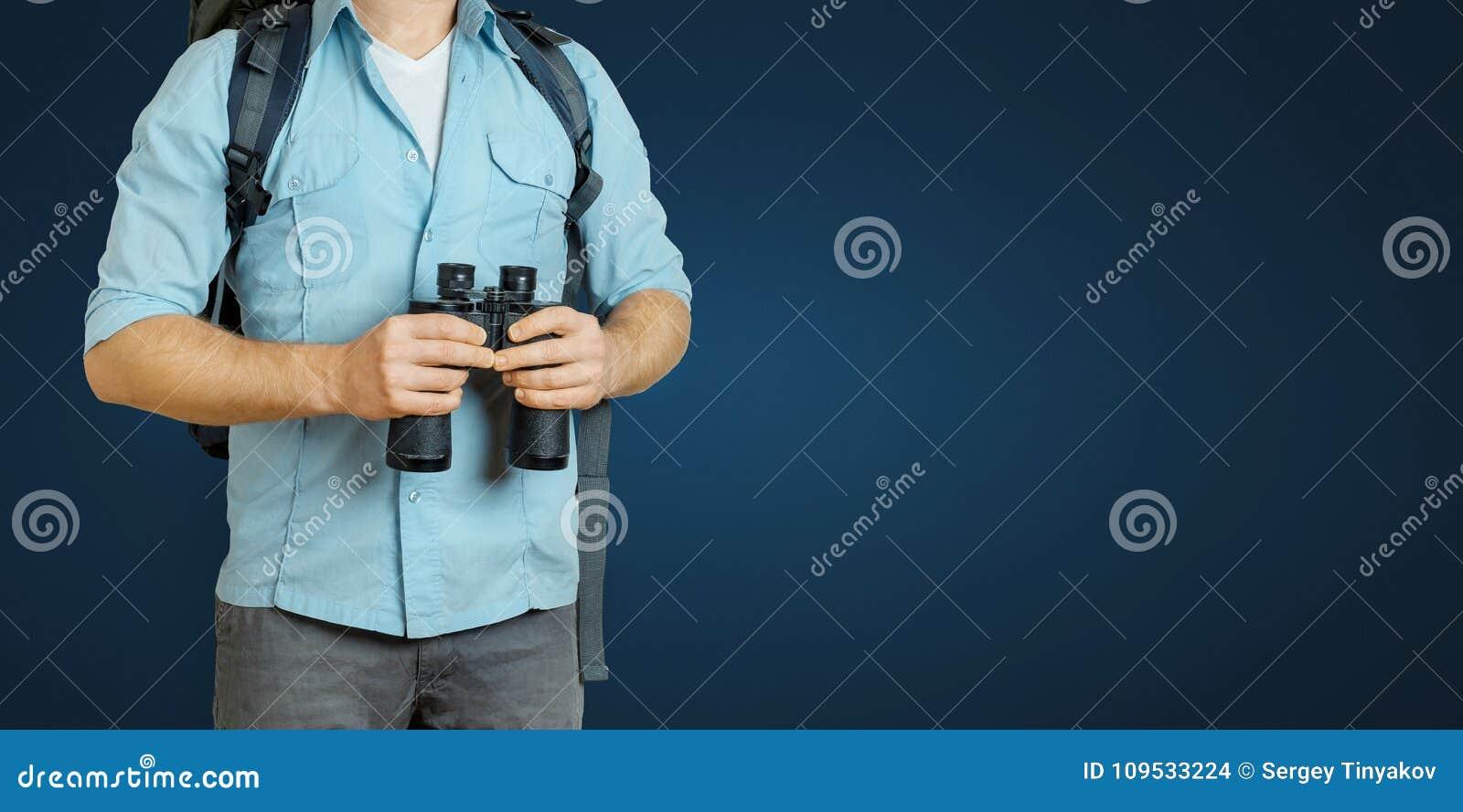 有背包和双筒望远镜的年轻旅客人寻找在蓝色背景的方向 远足旅游业旅途概念