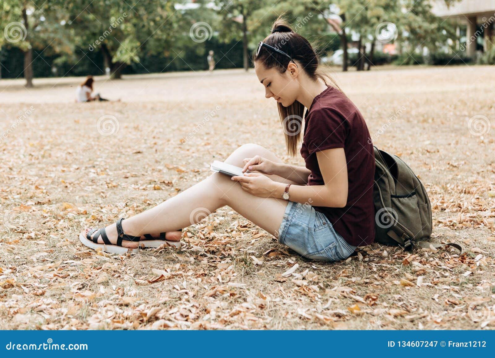 有背包的一少女在秋天公园坐并且使用片剂