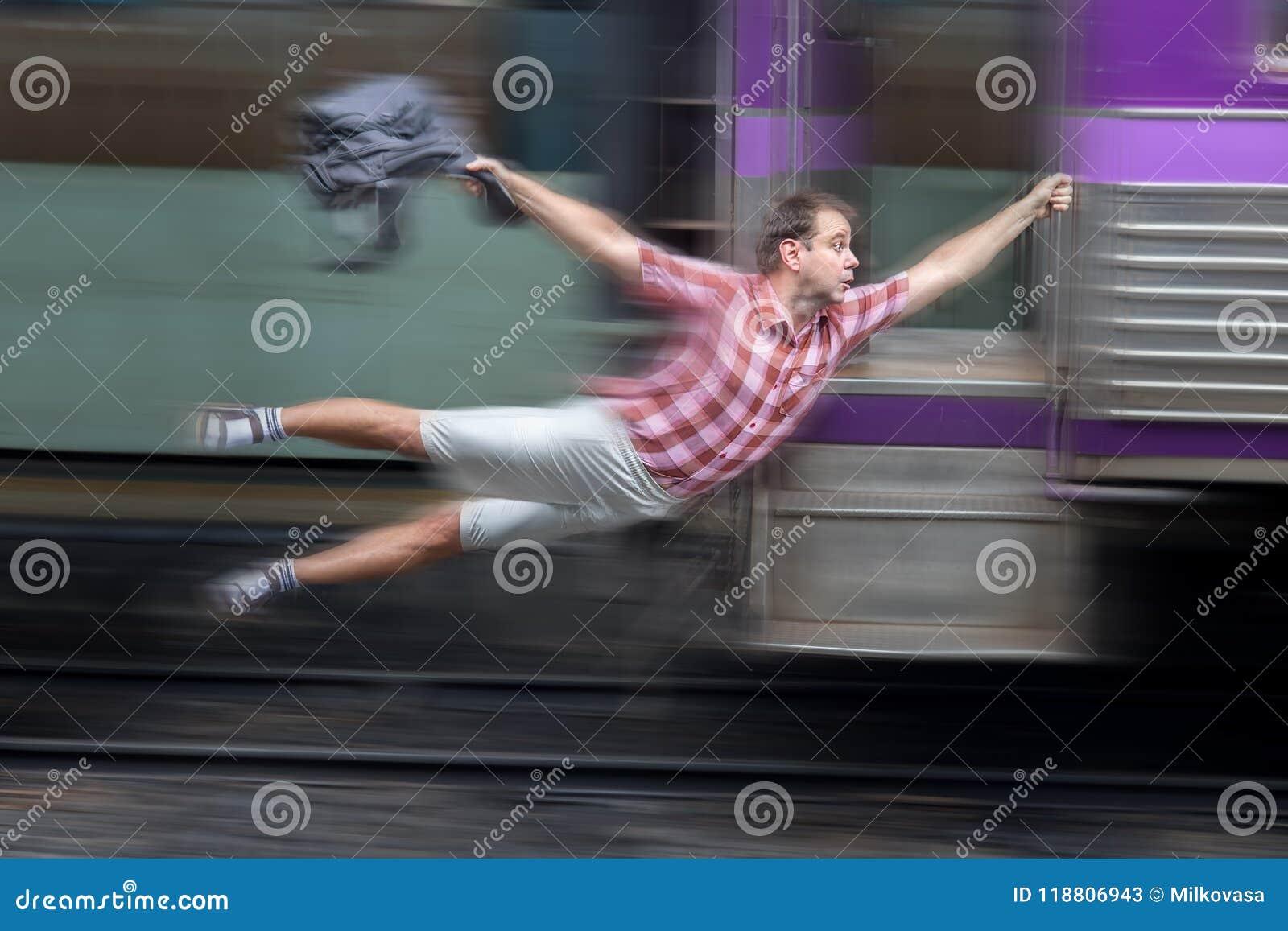 有背包的人在一列移动的火车后飞行