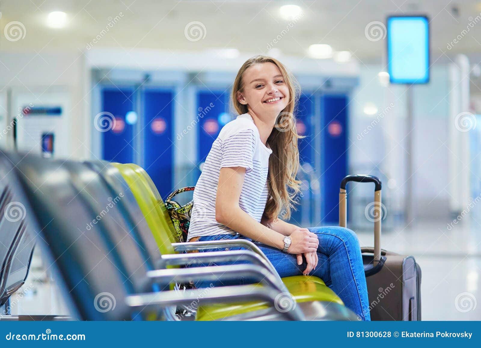有背包的美丽的年轻旅游女孩和在国际机场继续行李