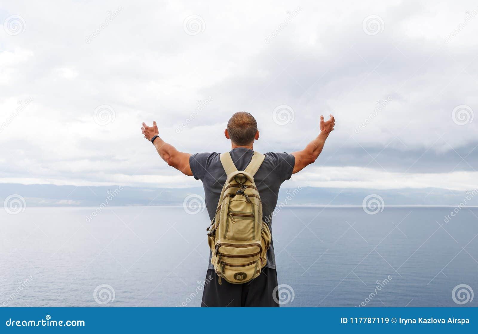 有背包立场的旅客在岸和看海用在空气的被举的手