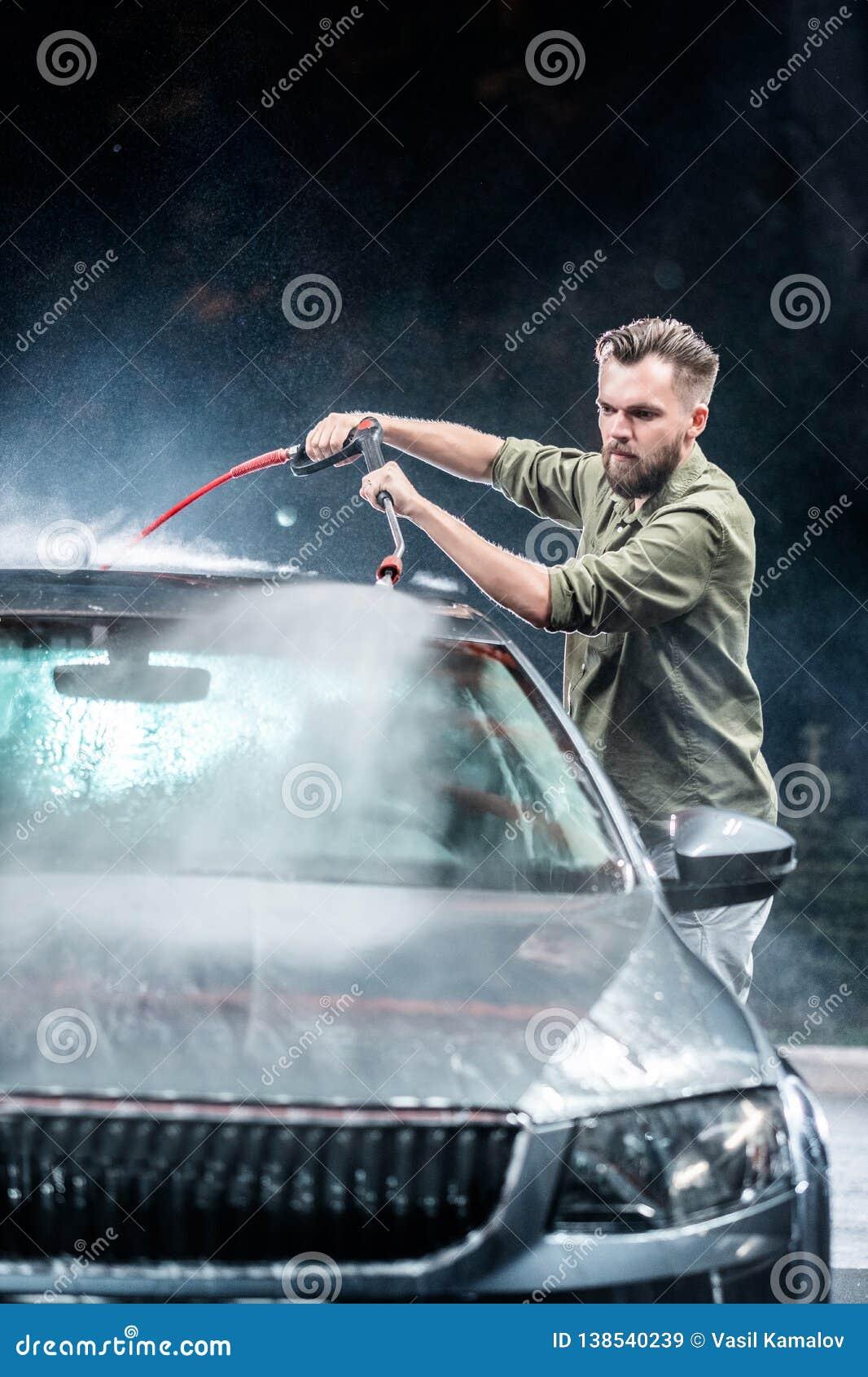 有胡子或汽车洗衣机的一个人在晚上洗涤有一台高压洗衣机的一辆灰色汽车在街道
