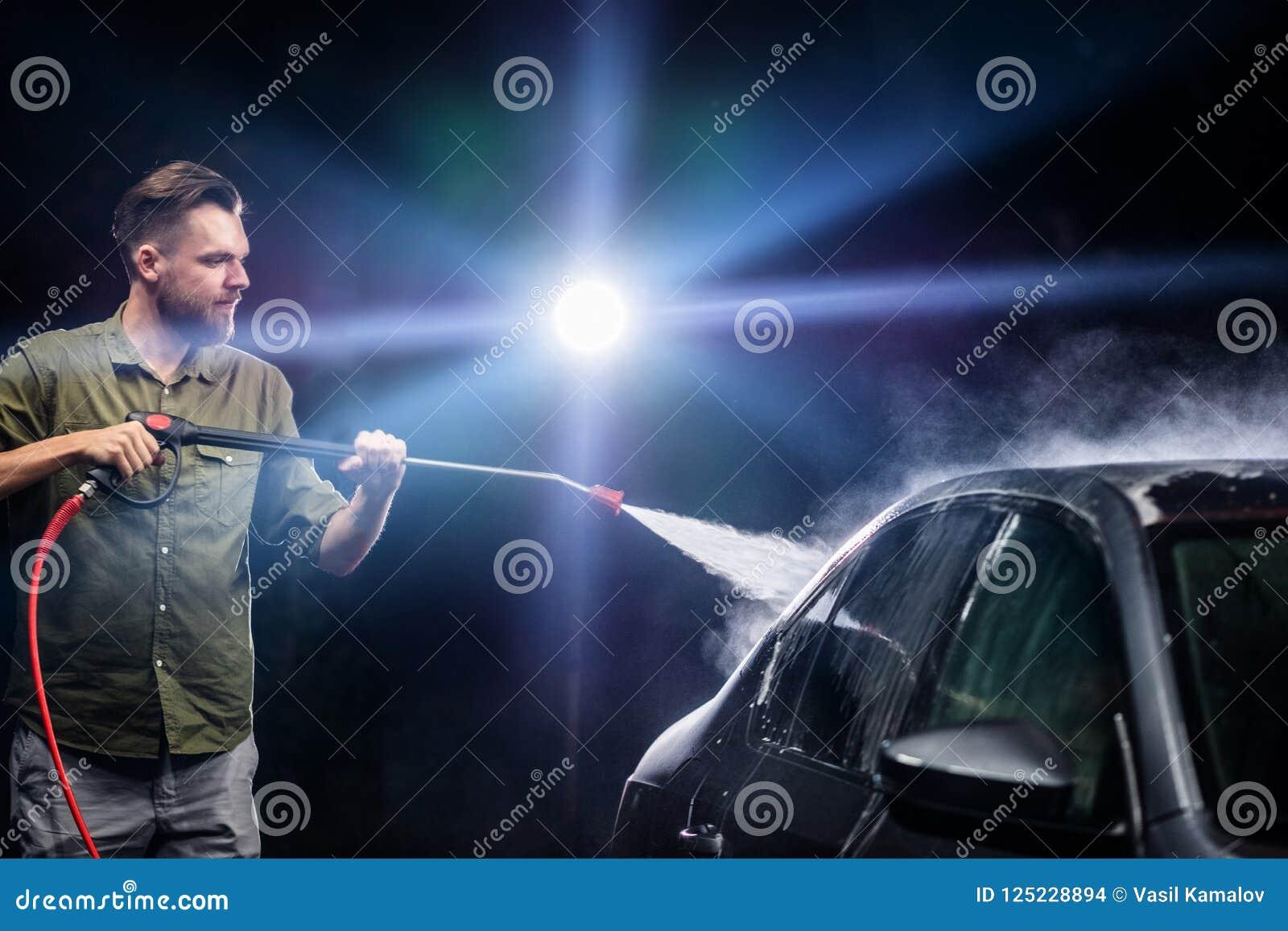 有胡子或汽车洗衣机的一个人在洗车的晚上洗涤有高压用具的一辆灰色汽车