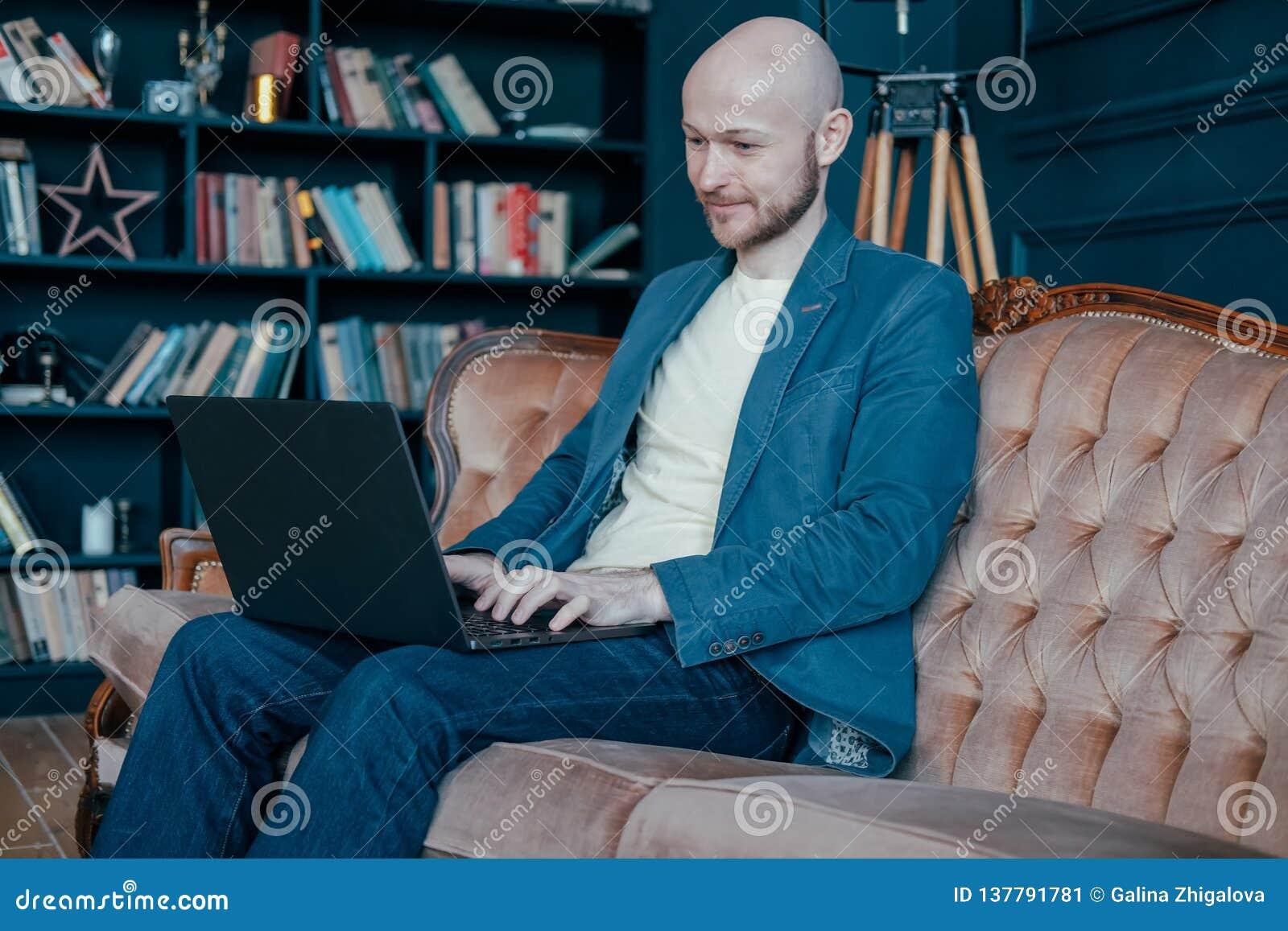 有胡子的可爱的成人成功的微笑的秃头人在运作在他富有的内阁的膝上型计算机的衣服