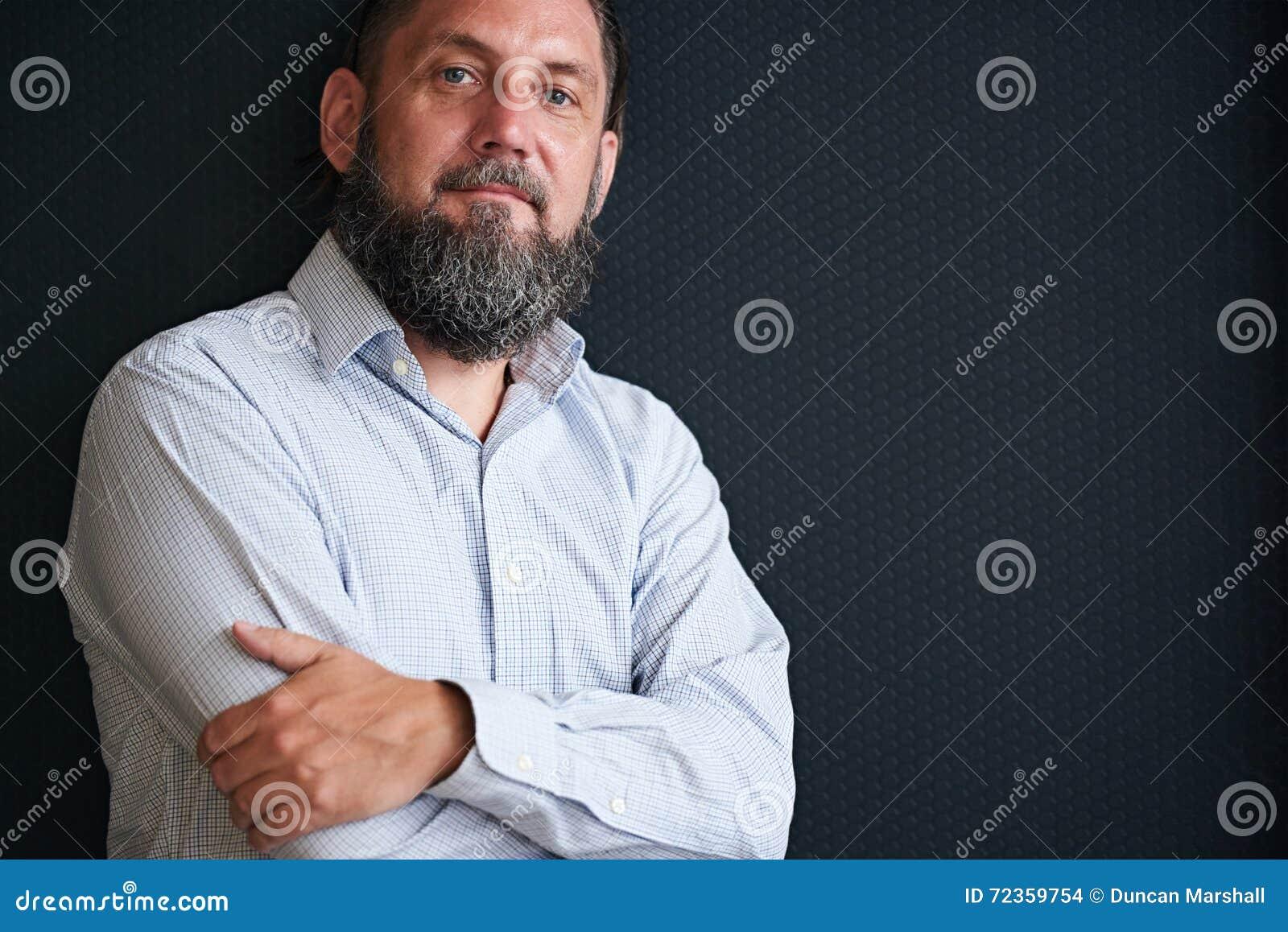 有胡子的坚固性看起来的成熟人反对黑织地不很细背景