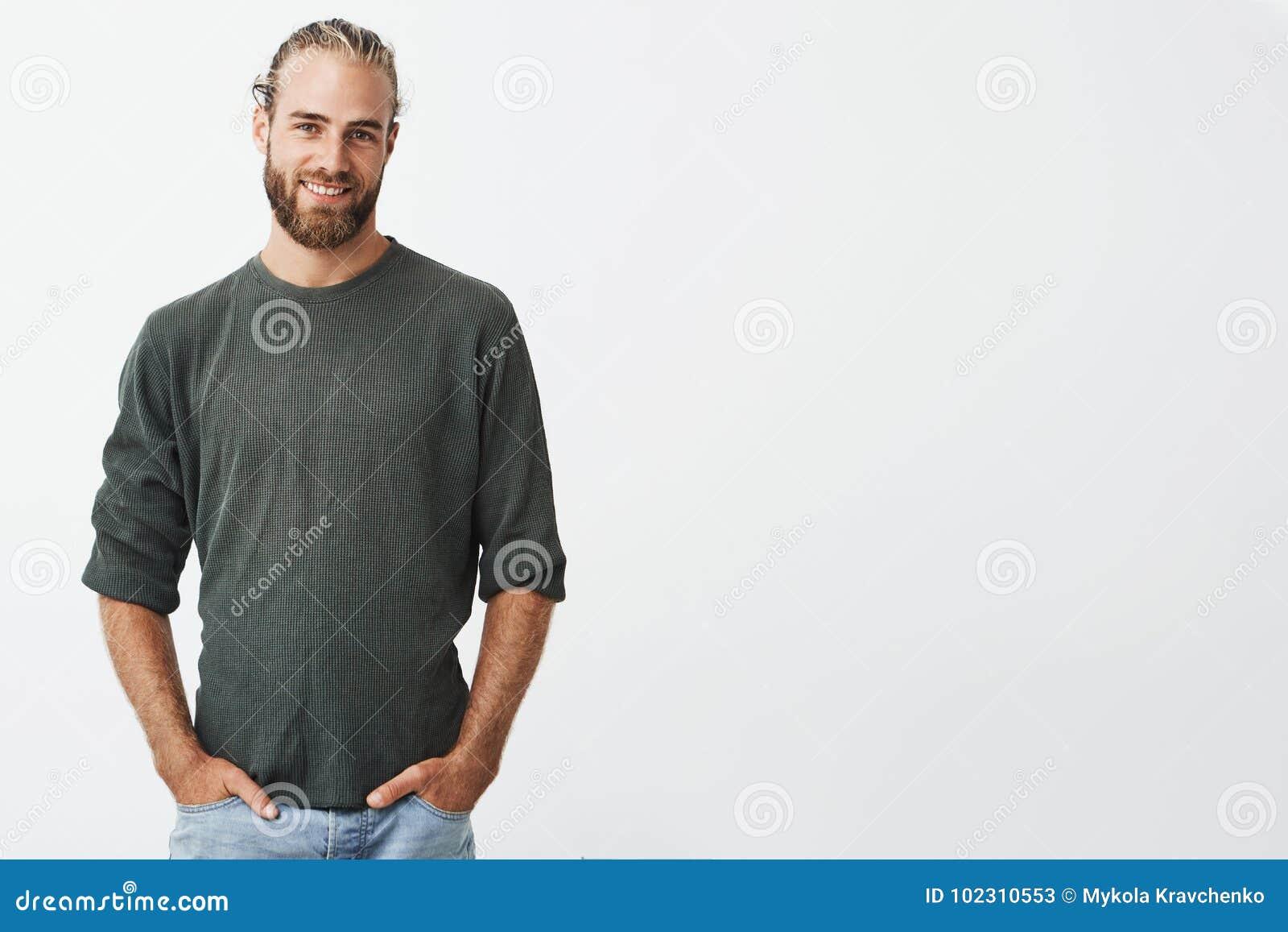 有胡子的英俊的北欧人和在灰色衬衣和牛仔裤微笑的时髦的发型,看在照相机,保留手