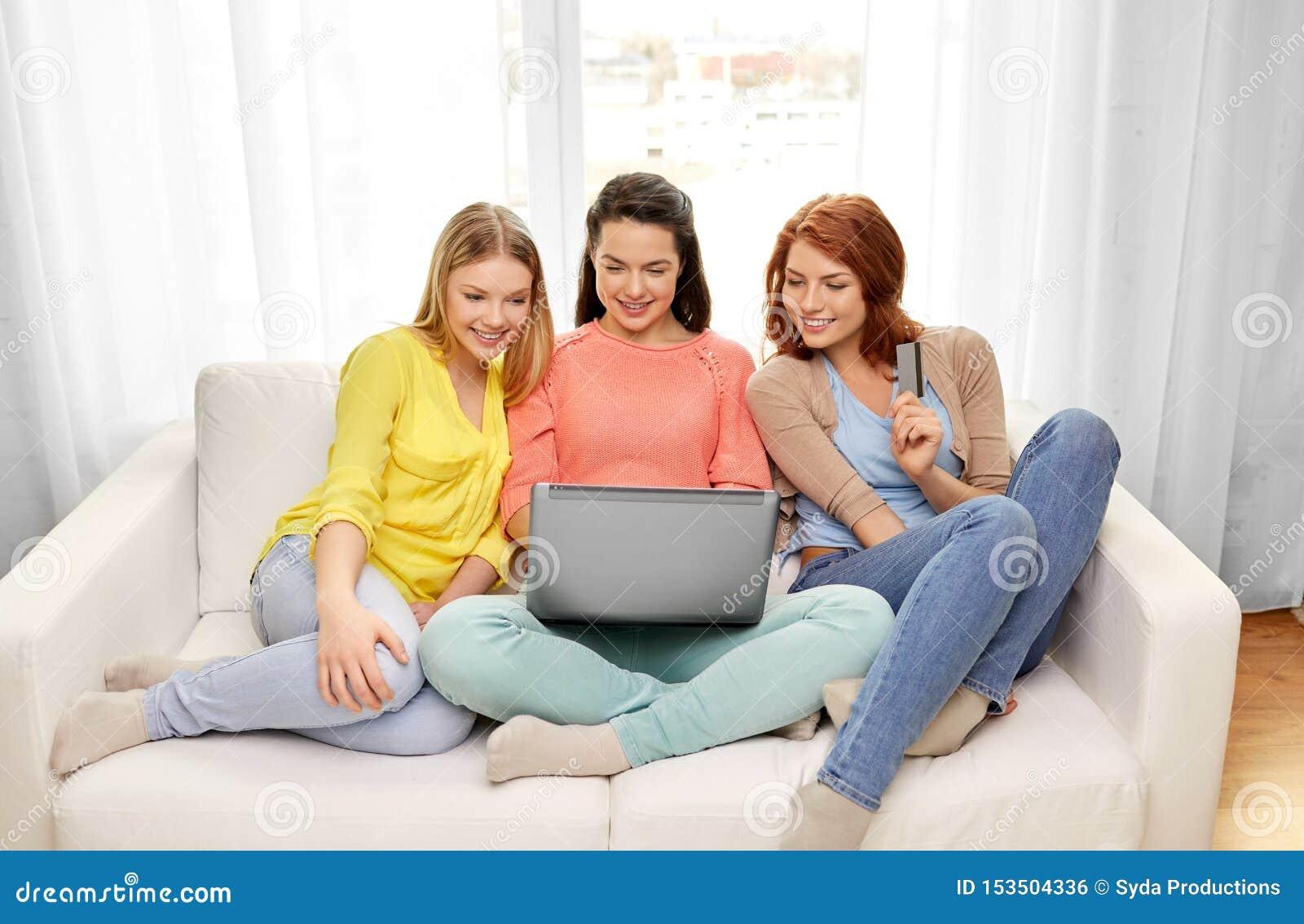 有膝上型计算机和信用卡的十几岁的女孩