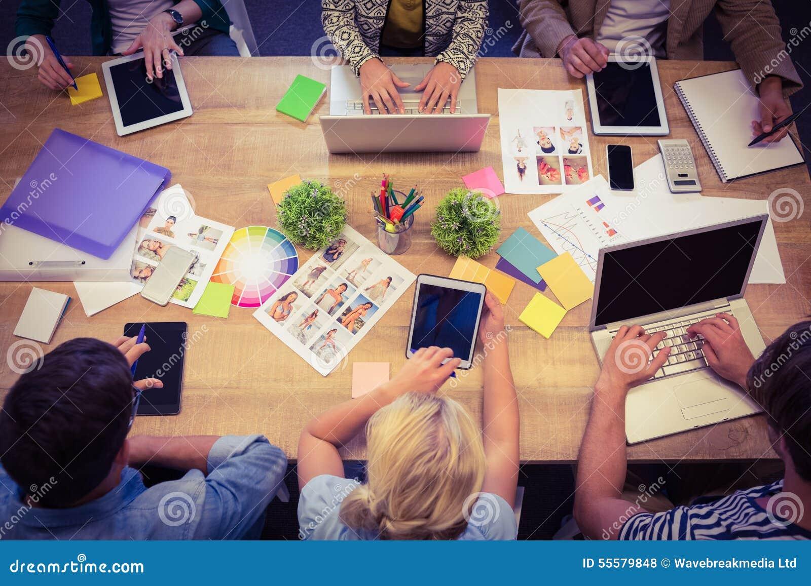 有膝上型计算机和数字式片剂办公室的创造性的同事