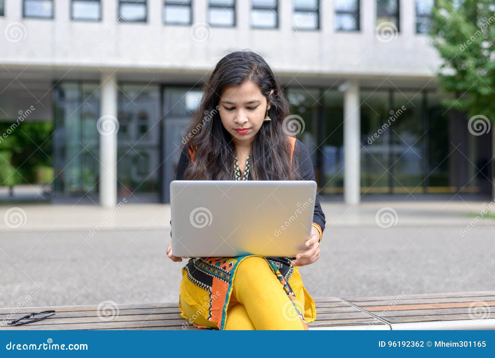 有膝上型计算机的严肃的印地安女孩