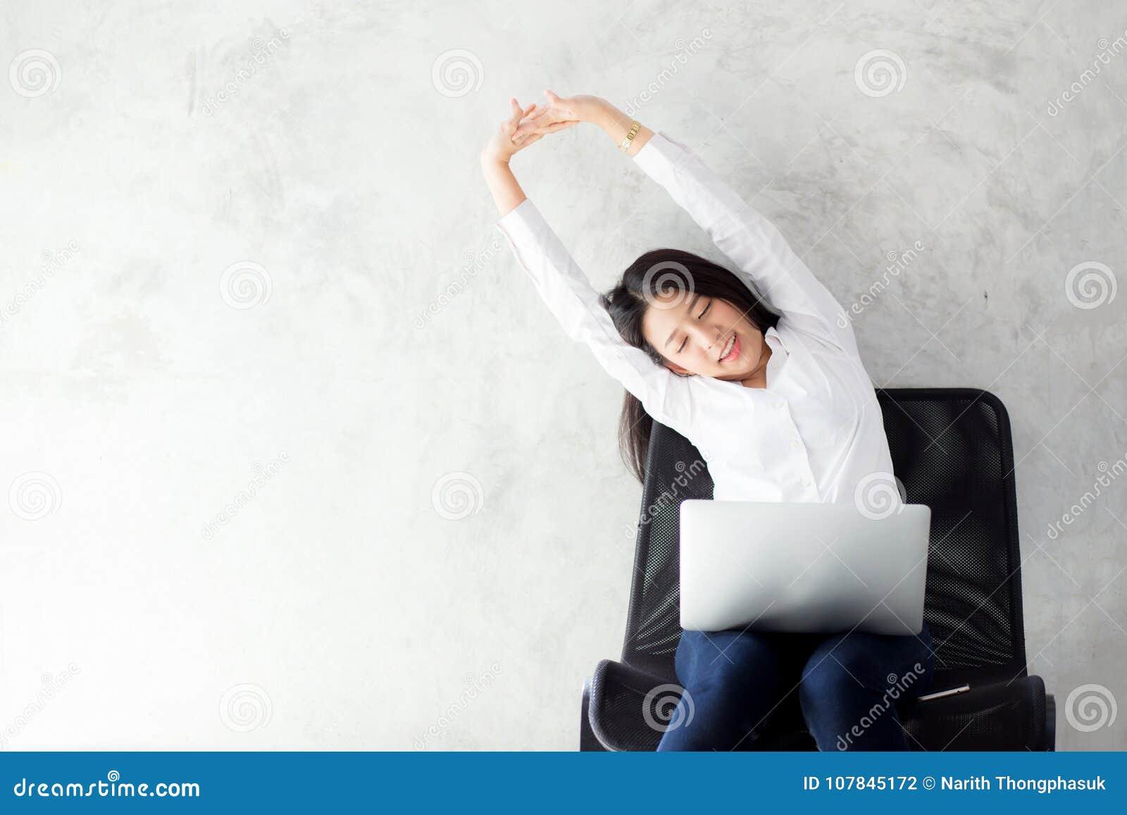 有膝上型计算机舒展的美丽的年轻亚裔妇女和锻炼在工作成功以后放松