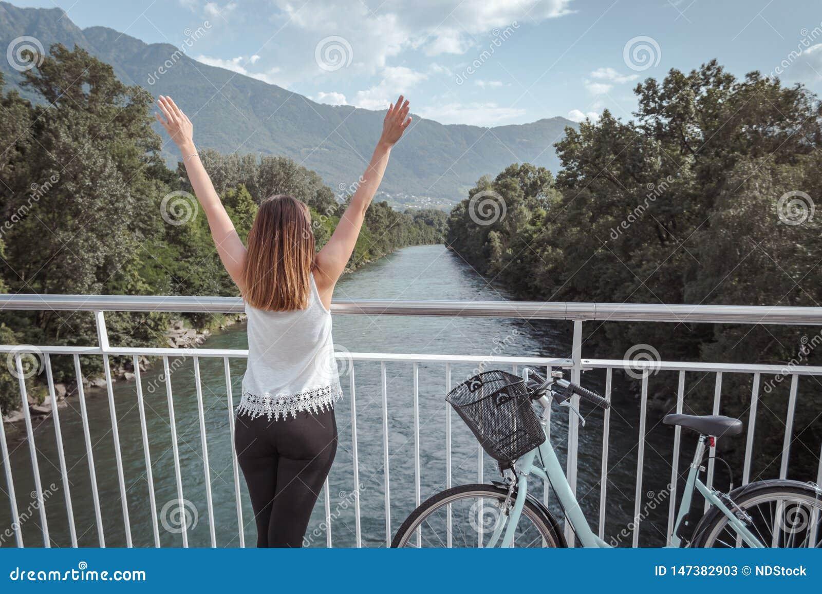 有自行车的年轻可爱的妇女在桥梁