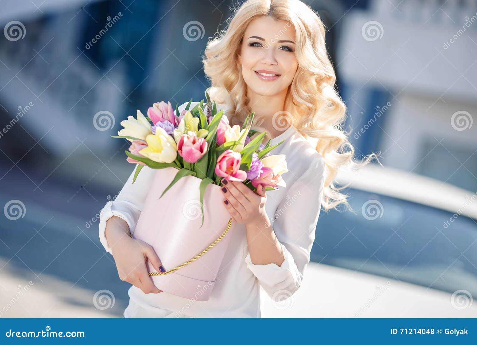 有花的美丽的金发碧眼的女人在礼物盒