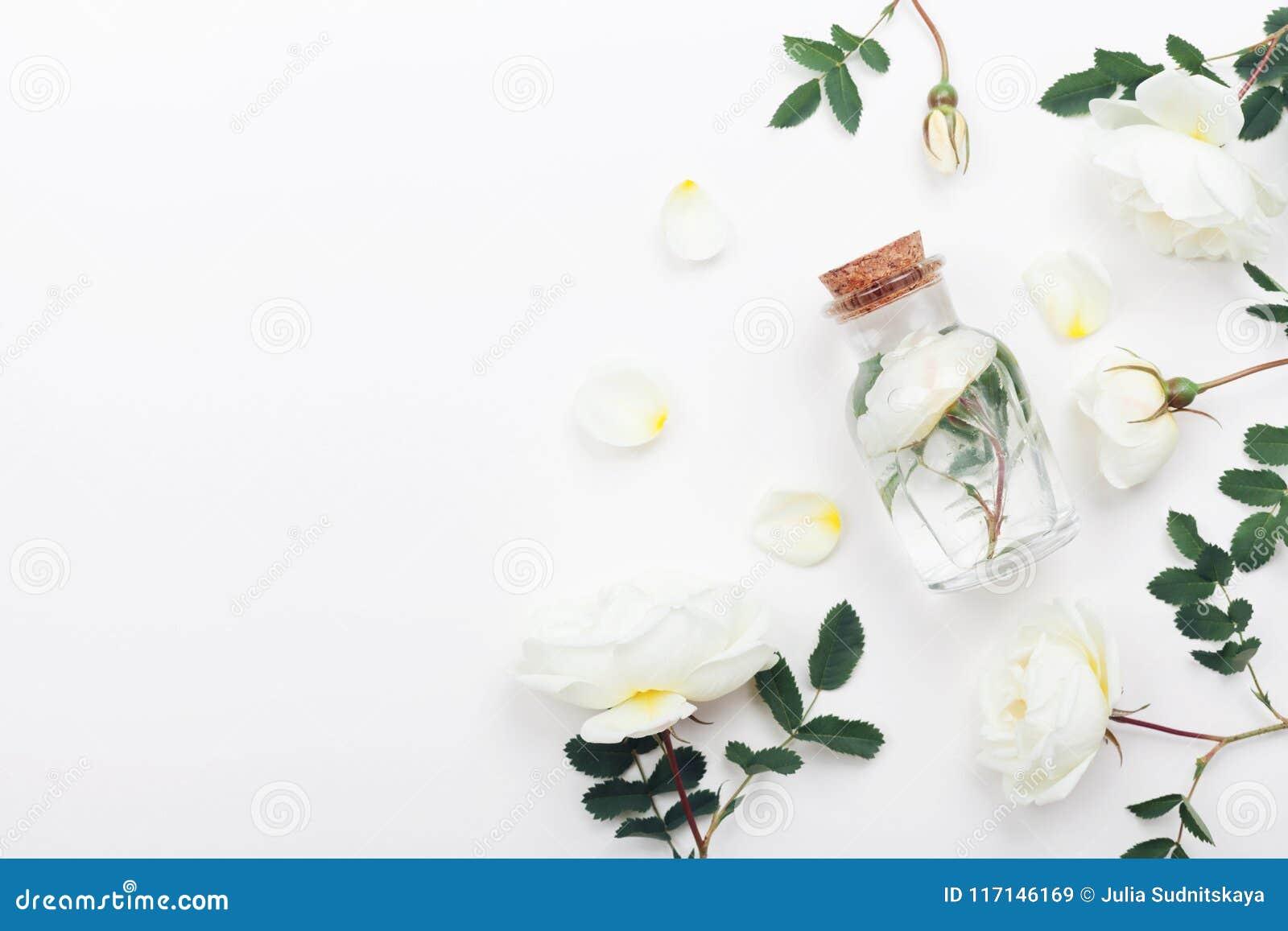 有芳香水和白色玫瑰的玻璃瓶子为温泉和芳香疗法开花 顶视图和平的位置样式