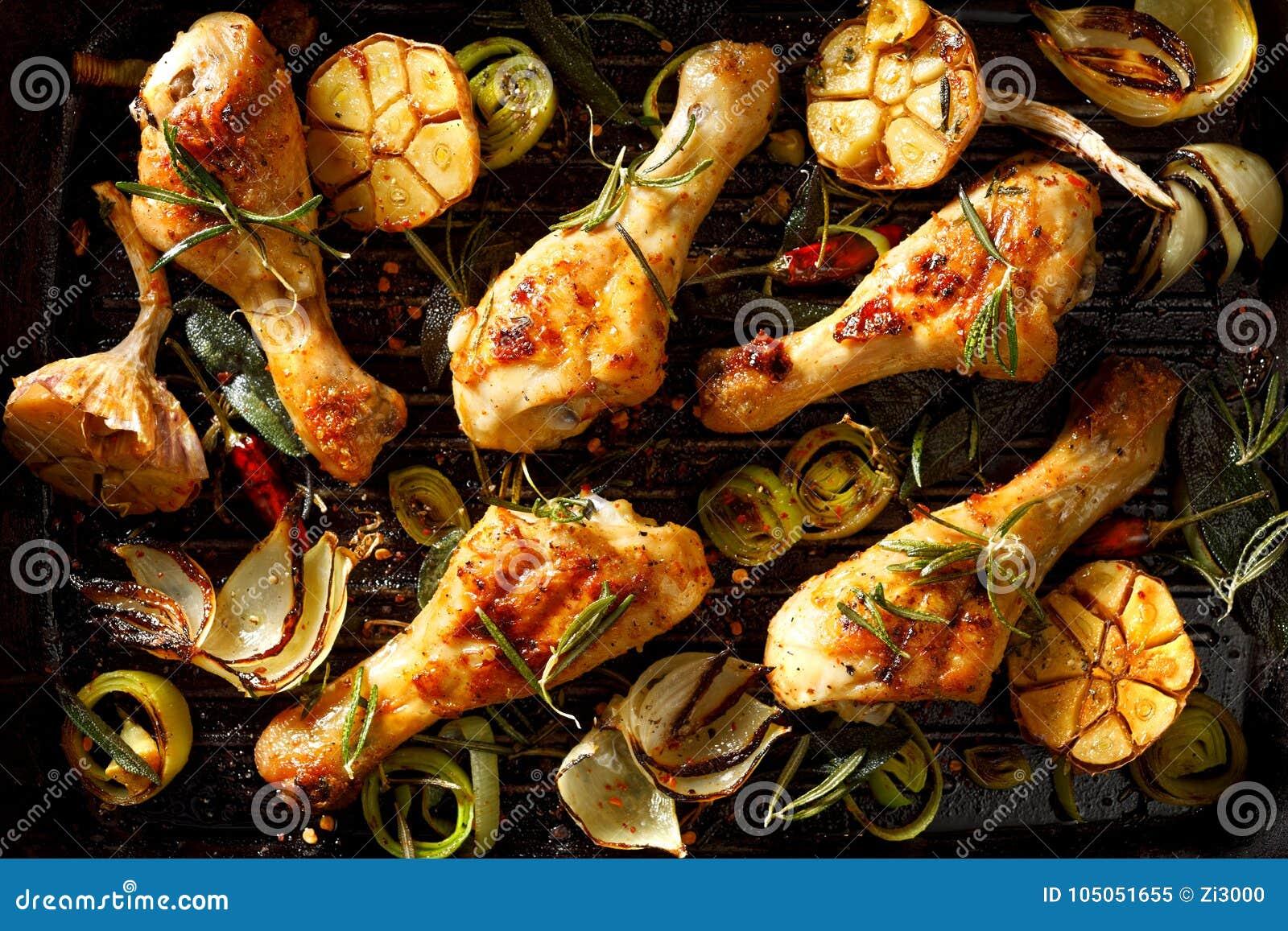 有芳香迷迭香、大蒜、葱、韭葱和香料的加法的烤鸡腿在格栅板材