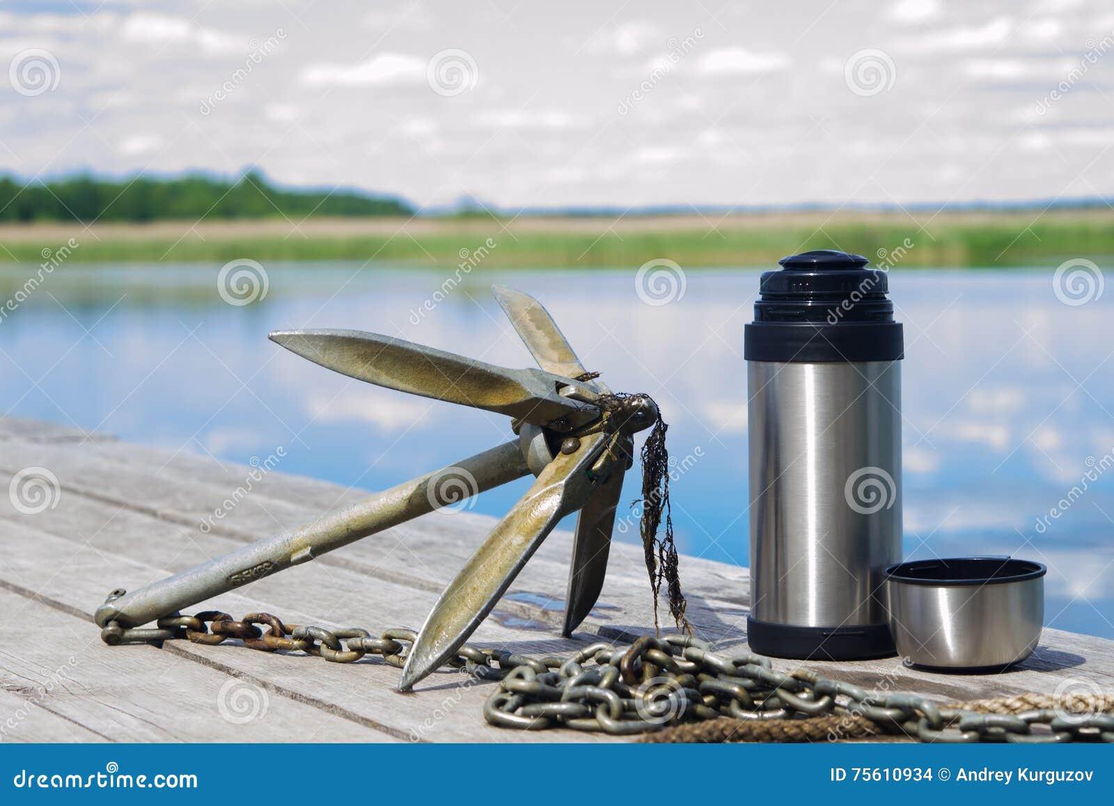 有茶热水瓶的船锚在自然背景的在码头