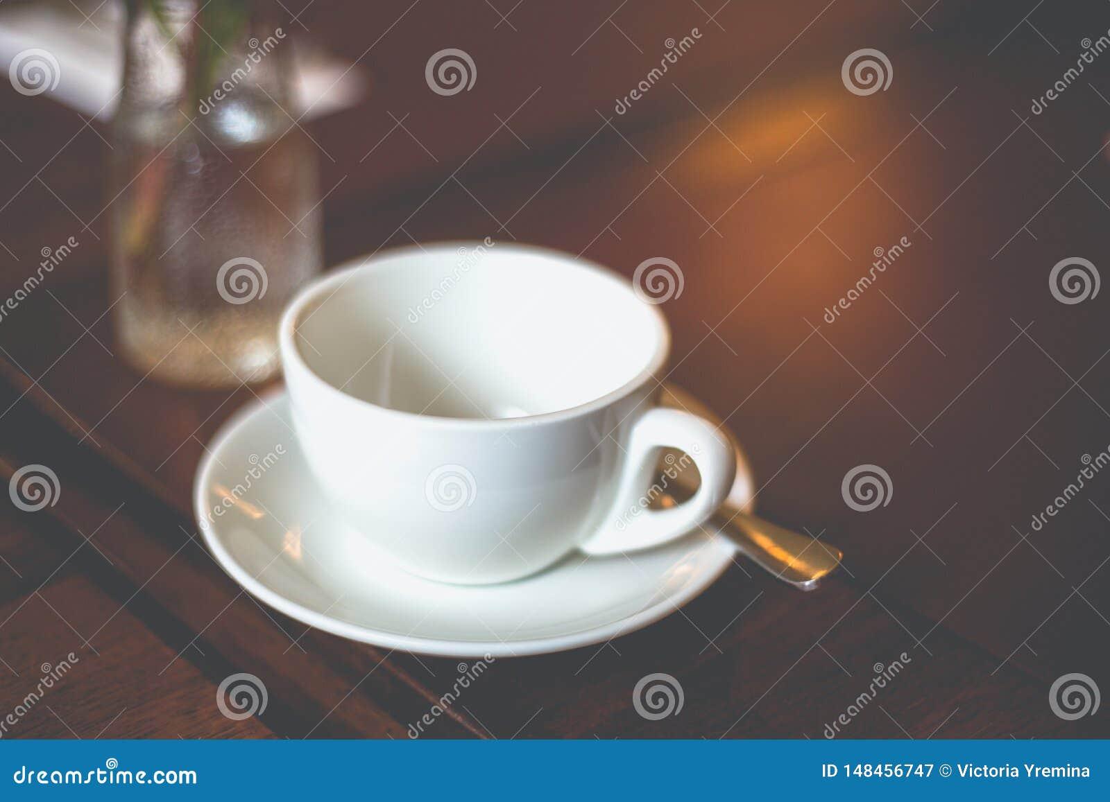有茶碟和匙子的特写镜头空的白色杯子在桌上