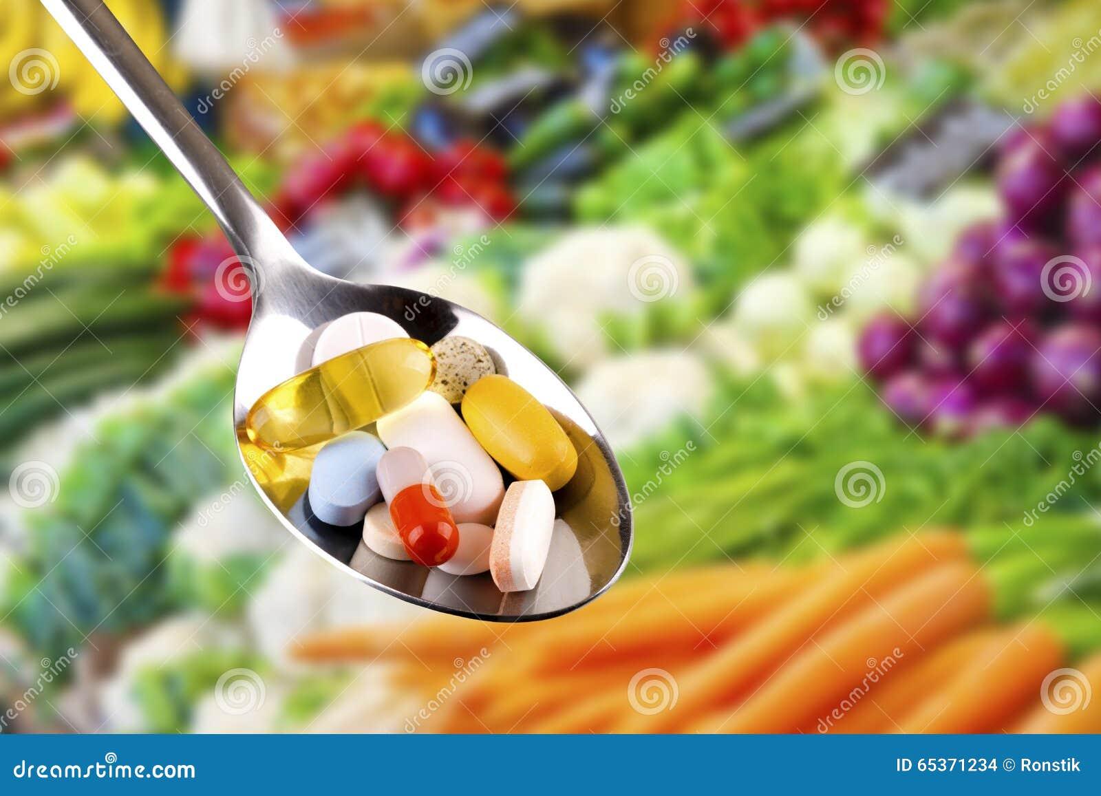有药片的,在菜背景的膳食补充剂匙子