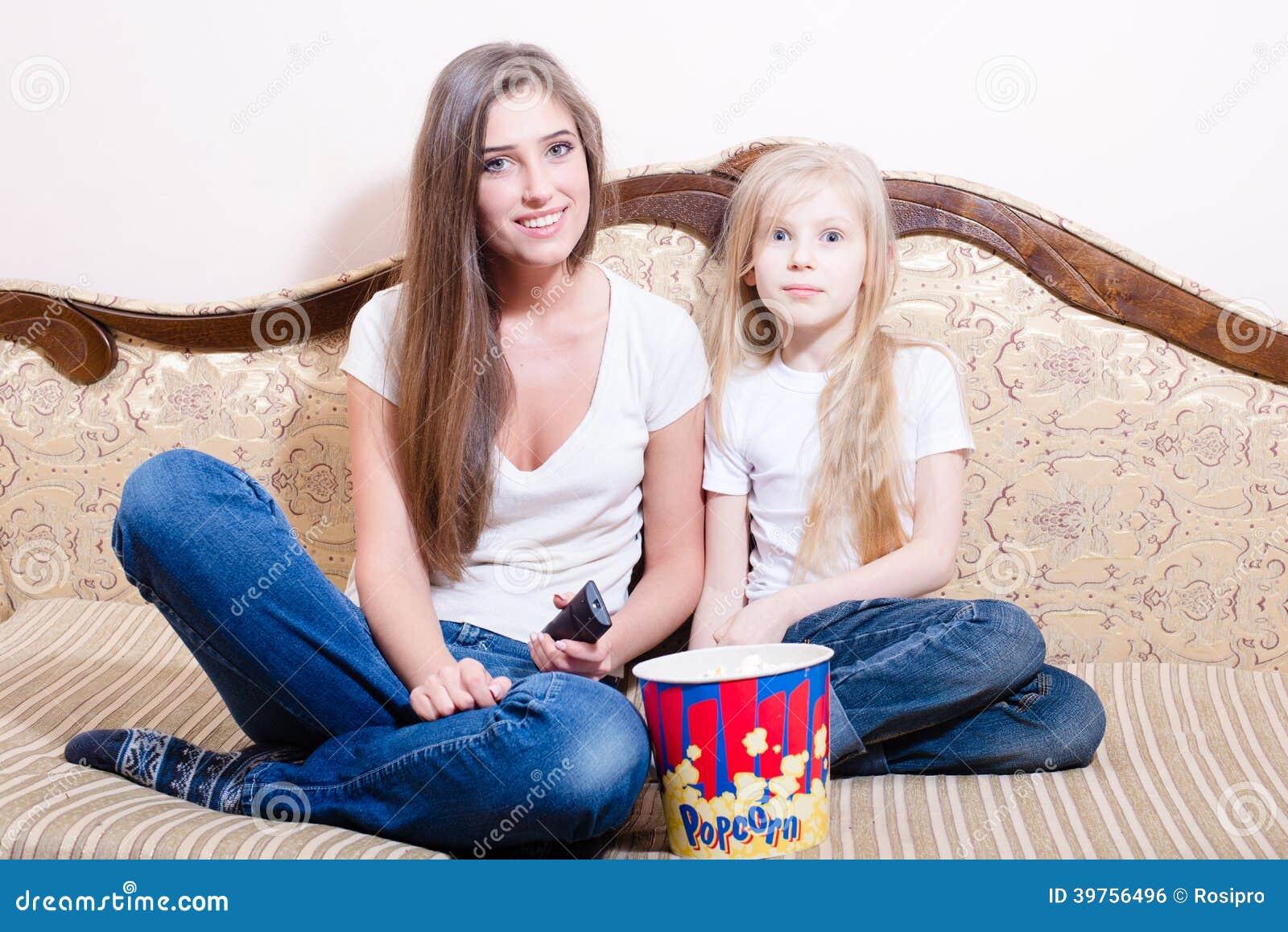 有获得乐趣坐&观看电影的女孩的少妇,吃玉米花,愉快的微笑的&看的照相机