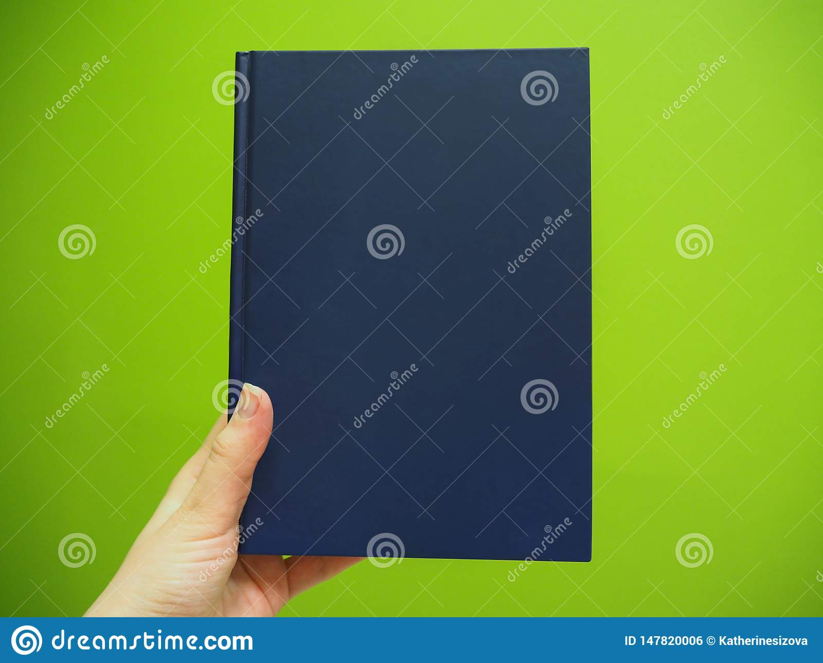 有蓝皮书的妇女的手在绿色背景