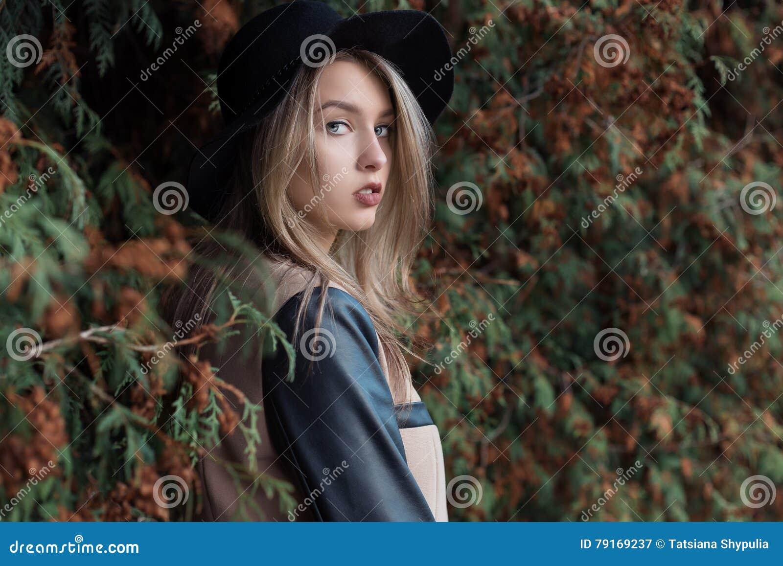 有蓝眼睛和充分的嘴唇的孤独的哀伤的相当逗人喜爱的白肤金发的女孩在黑帽会议和外套走在秋天森林里的