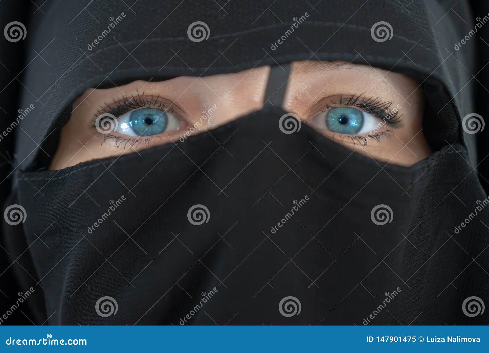 有蓝眼睛的年轻女人在紧密黑nibe burqa的女孩 r