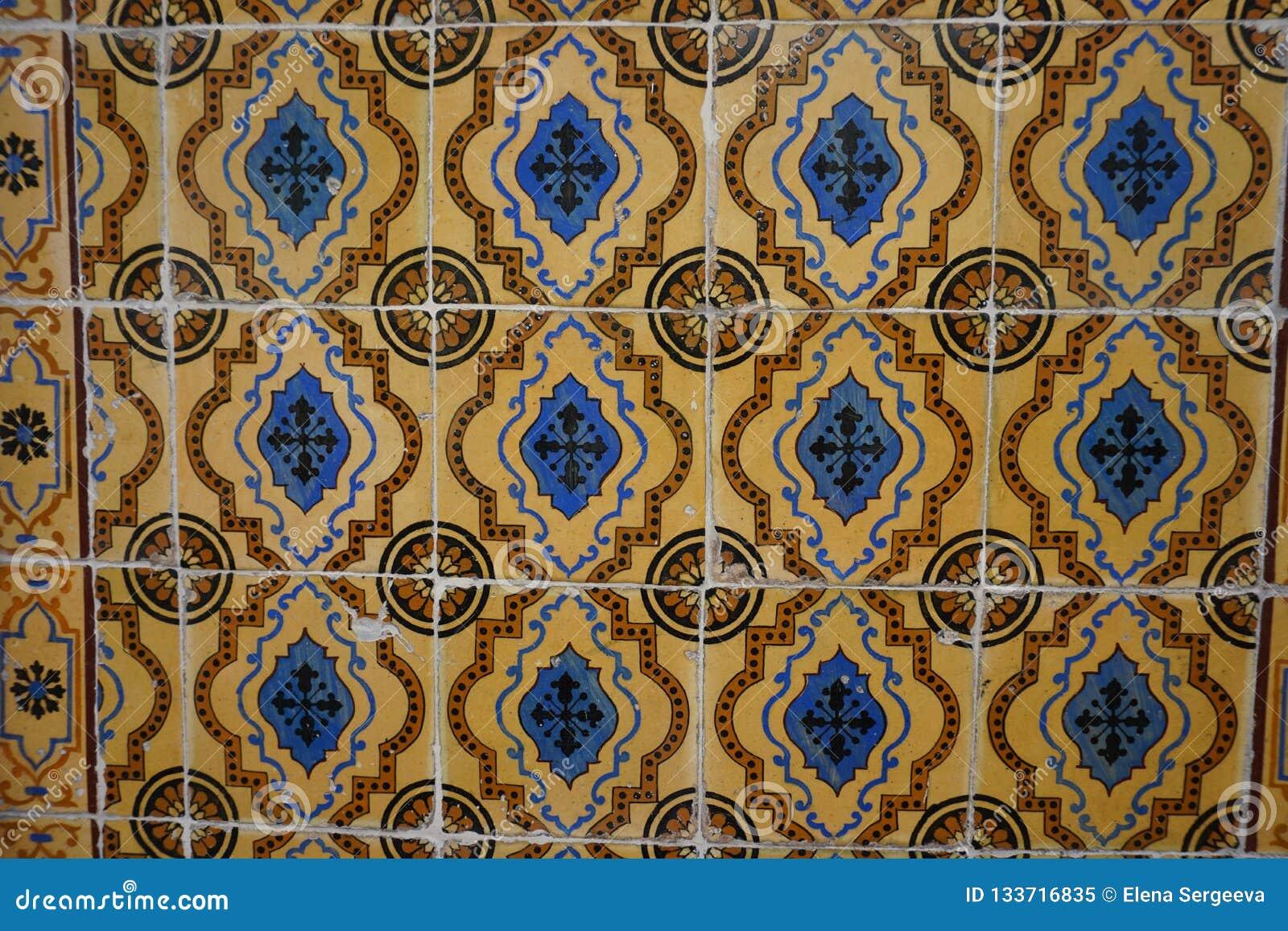 有蓝色和棕色装饰品的老橙色Azulejos瓦片