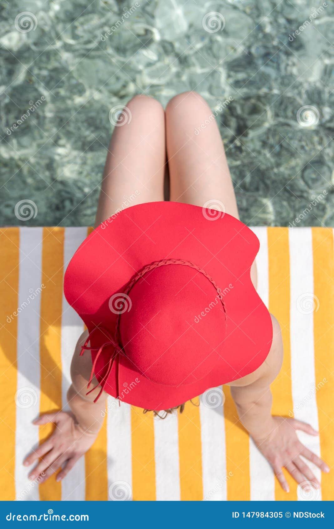 有蓝色比基尼泳装和红色帽子的年轻女人在透明的大海的一块毛巾