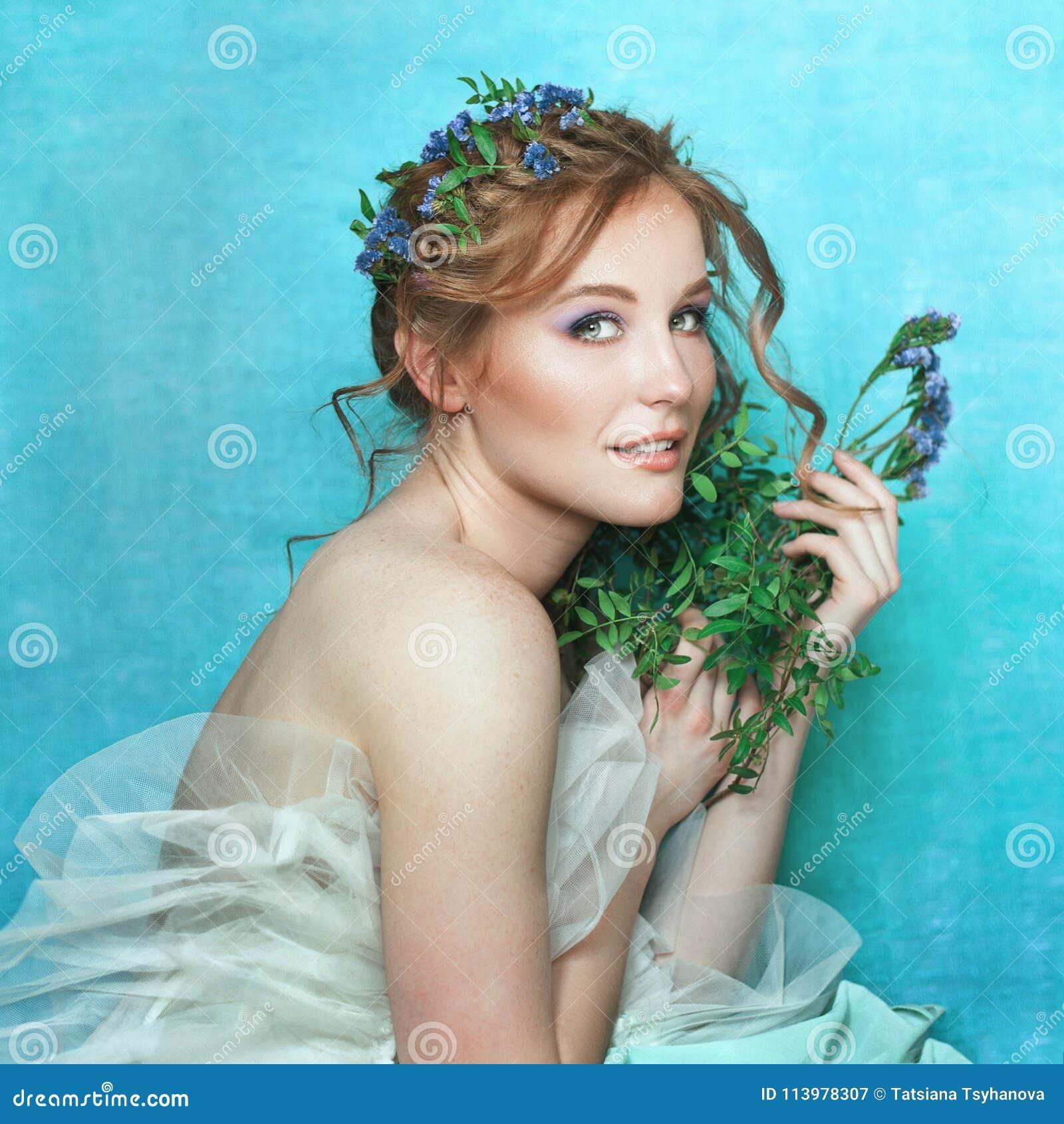 有蓝色花的年轻微笑的女孩在浅兰的背景 春天美景画象