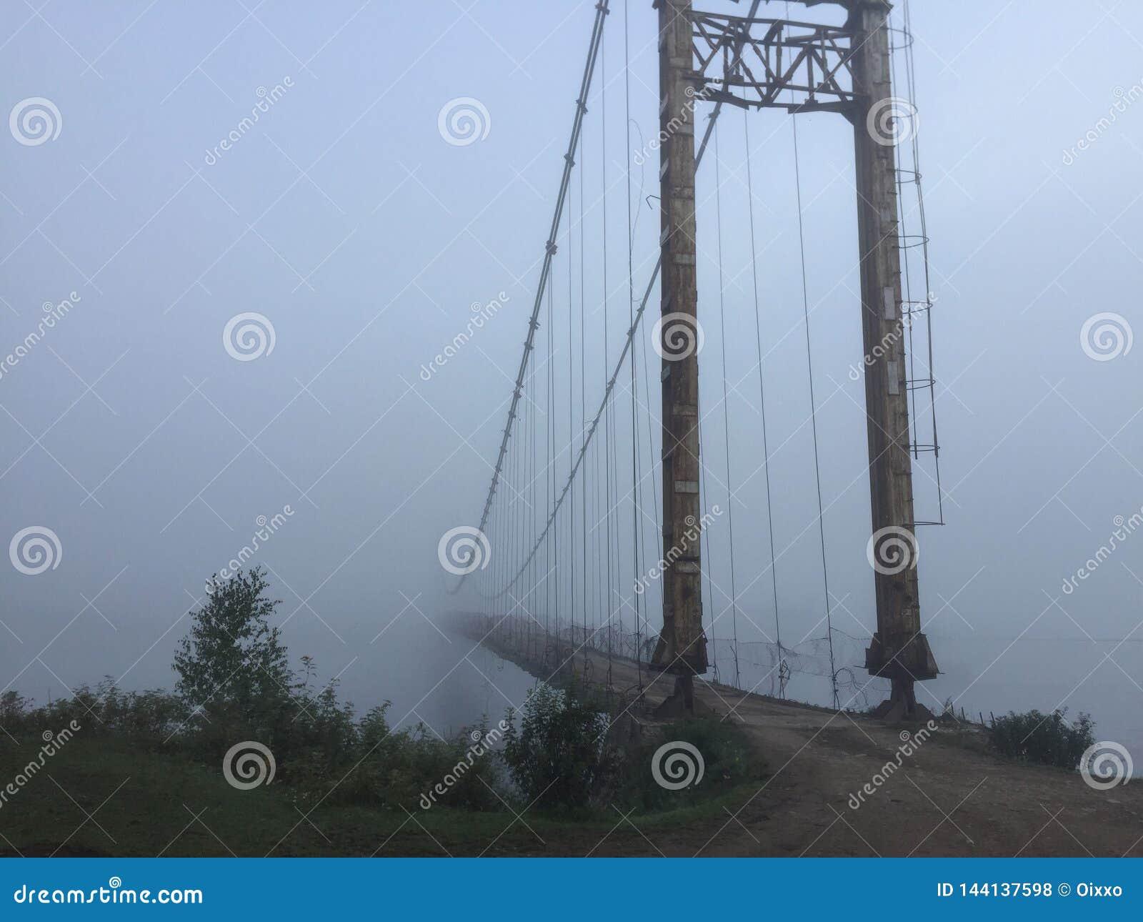 有薄雾的吊桥雾视图 阿尔泰村庄桥梁 E