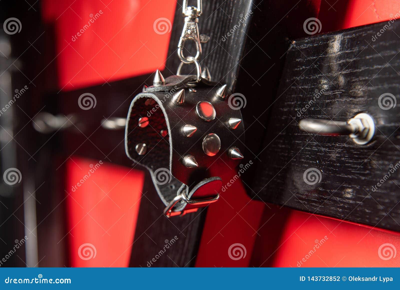 有螺柱的皮革手铐在木十字架