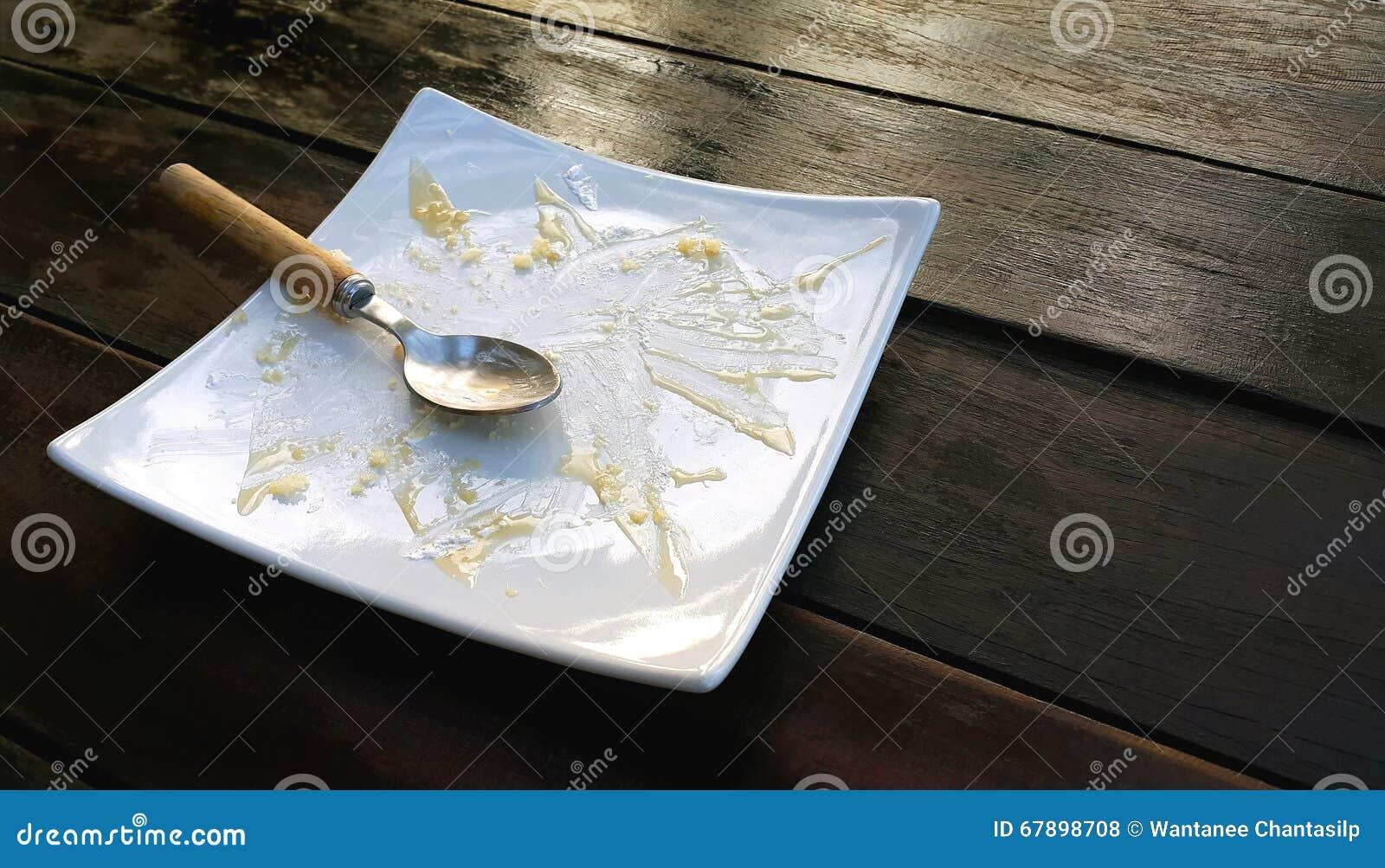 有被吃的蛋糕和使用的匙子碎屑的空的板材