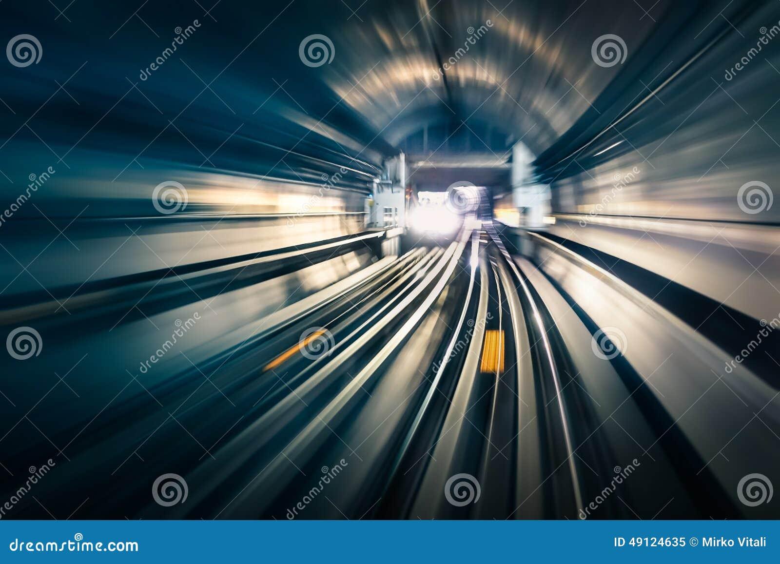 有被弄脏的轻的轨道的地铁隧道与在相反方向的到达的火车-现代地铁
