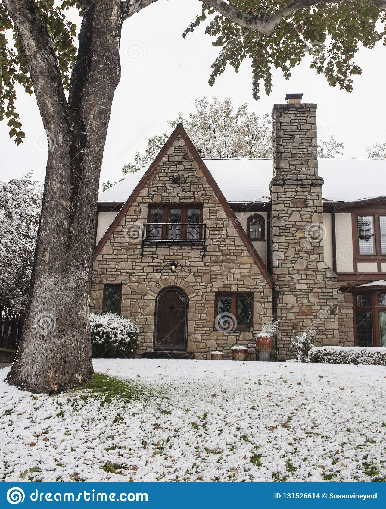 有被成拱形的门和托特样式行间空格特别大的玻璃金刚石盘区窗口的俏丽的岩石房子在降雪期间