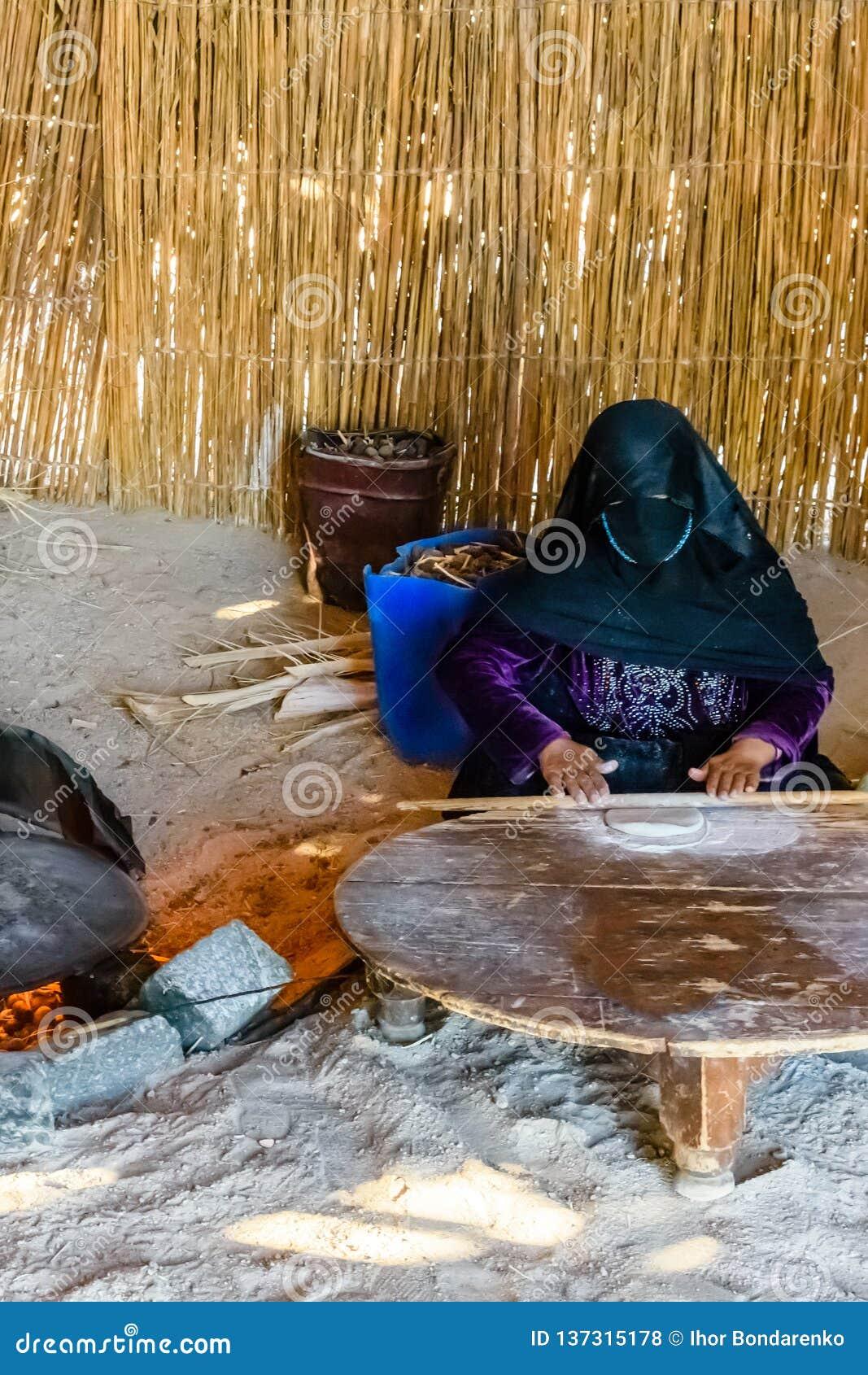 有被掩没的面孔的年轻回教妇女烹调在一所流浪的住宅的面包