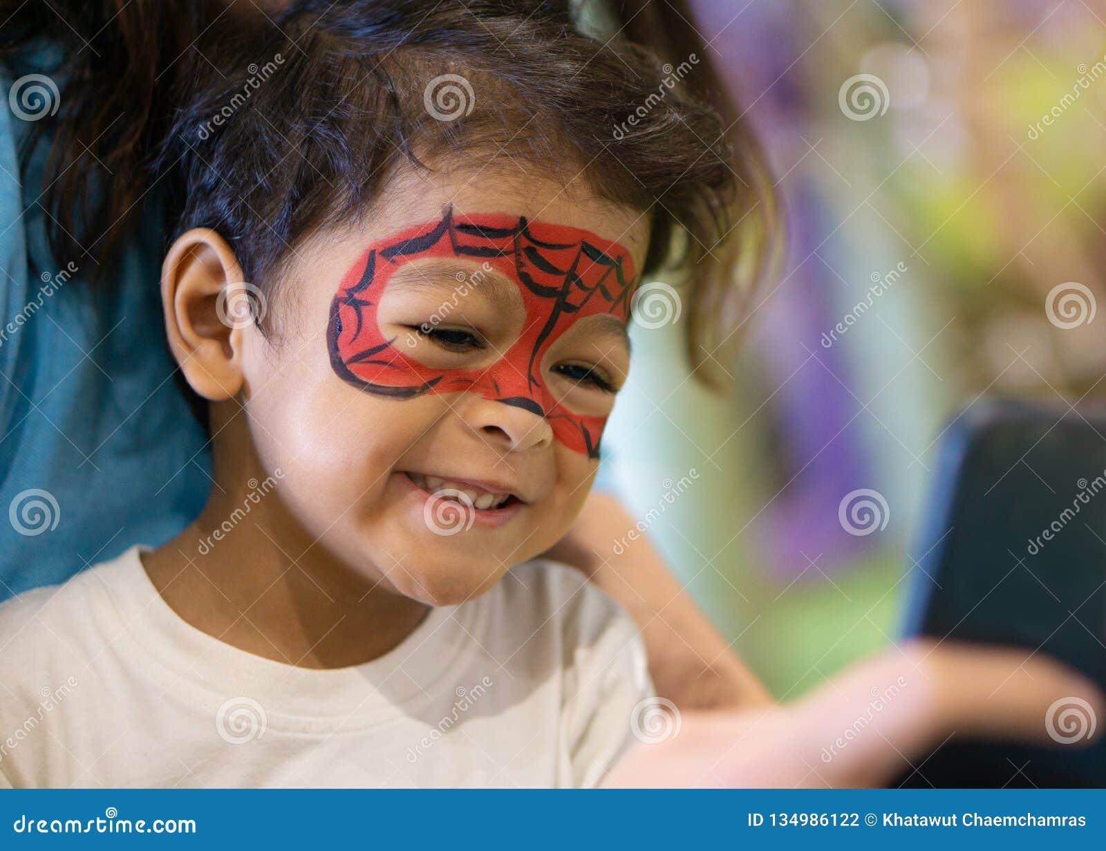有被绘的面孔的亚裔孩子男孩作为蜘蛛
